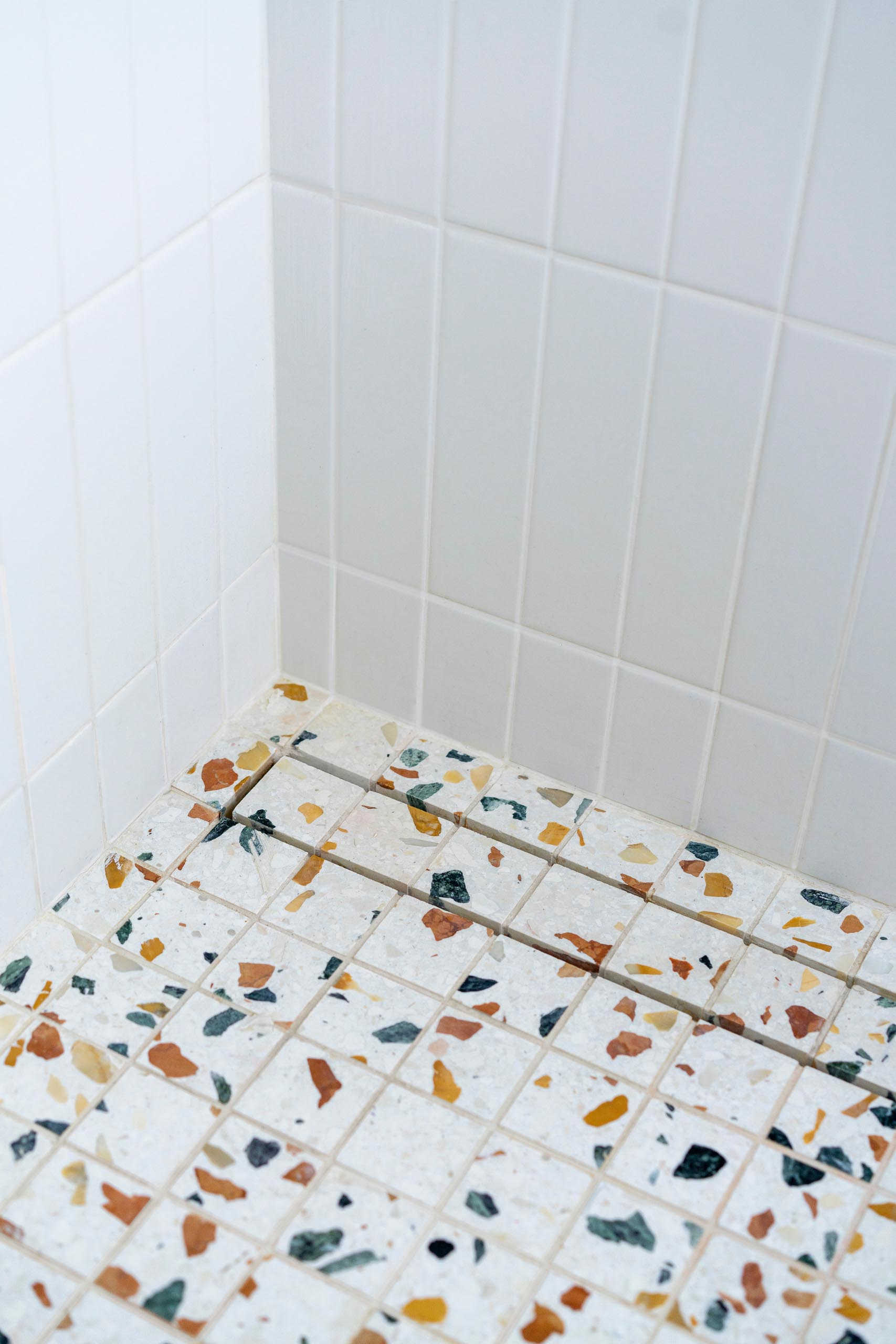 In this modern master bedroom bathroom, the shower features simple white tiles and a colorful terrazzo floor.