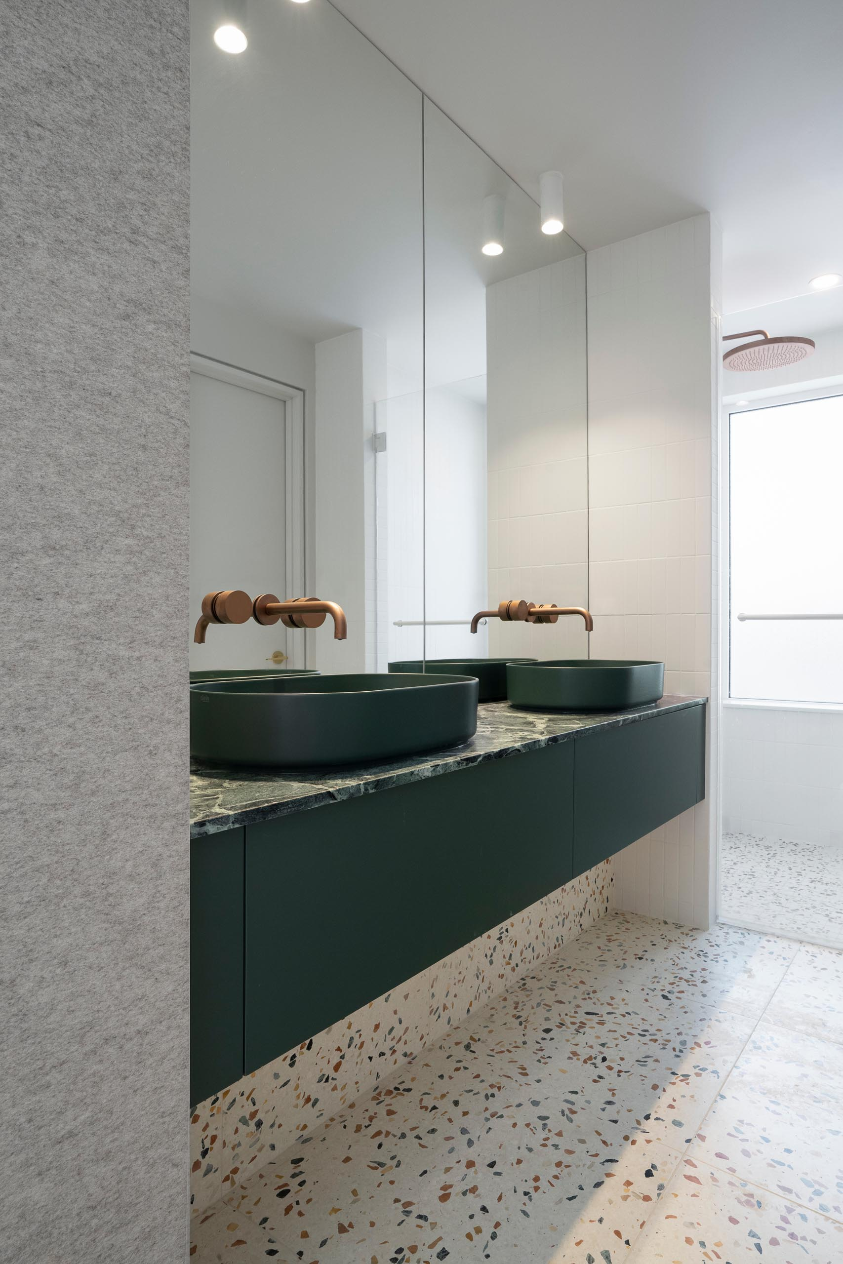 In this modern master bathroom, the Verde Saint-Denis marble countertop, emerald green sinks, and warm natural felt walls also harmonize with the terrazzo flooring.