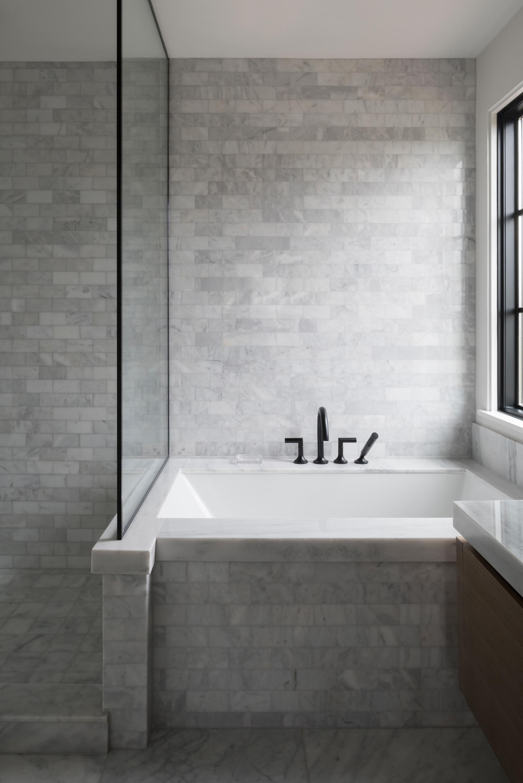 A modern bathroom with marble tiles, a built-in bathtub, and black framed glass shower screen.