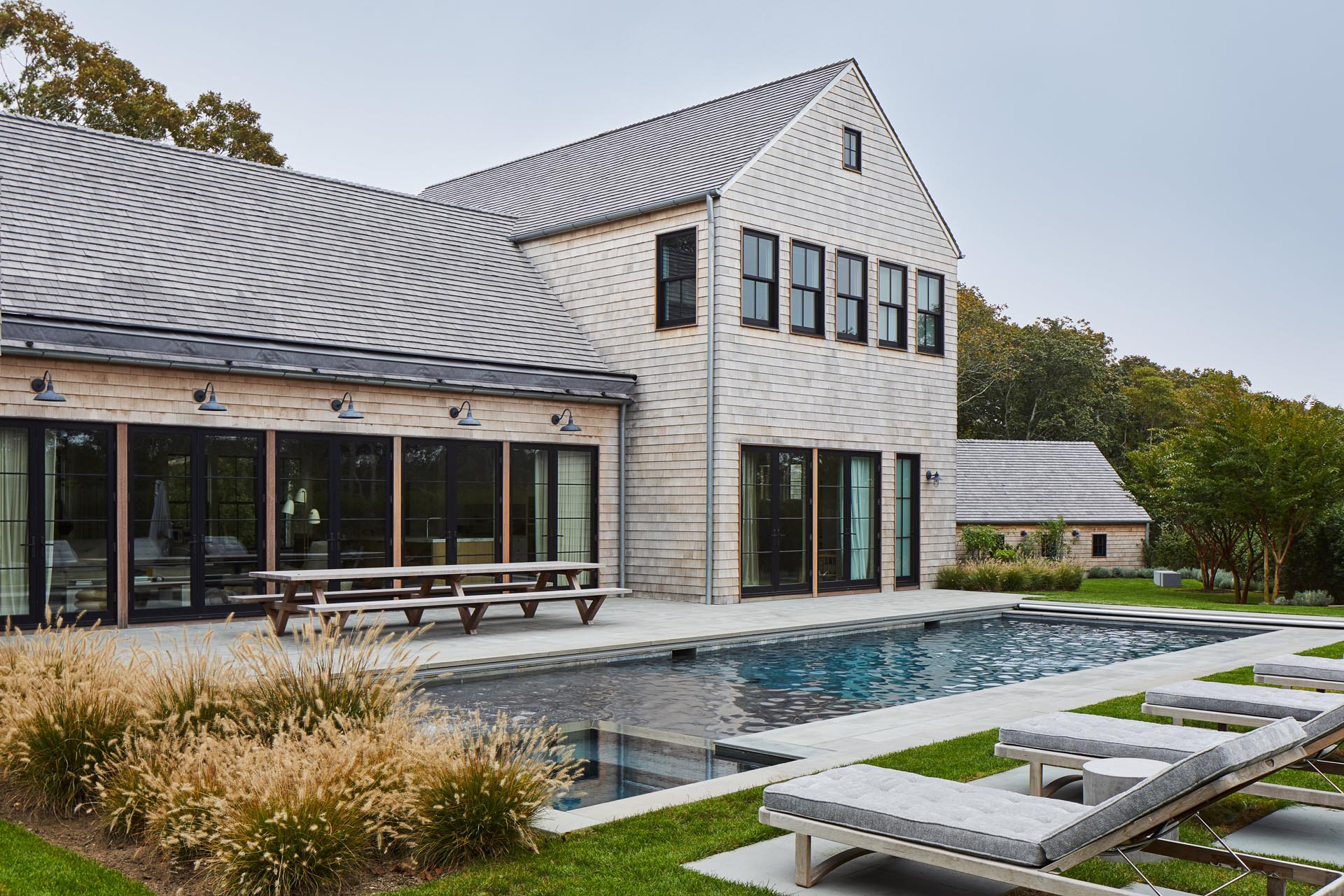 Located in Amagansett, New York, this modern farmhouse inspired home has a wood shingle exterior, as well as a swimming pool and patio.