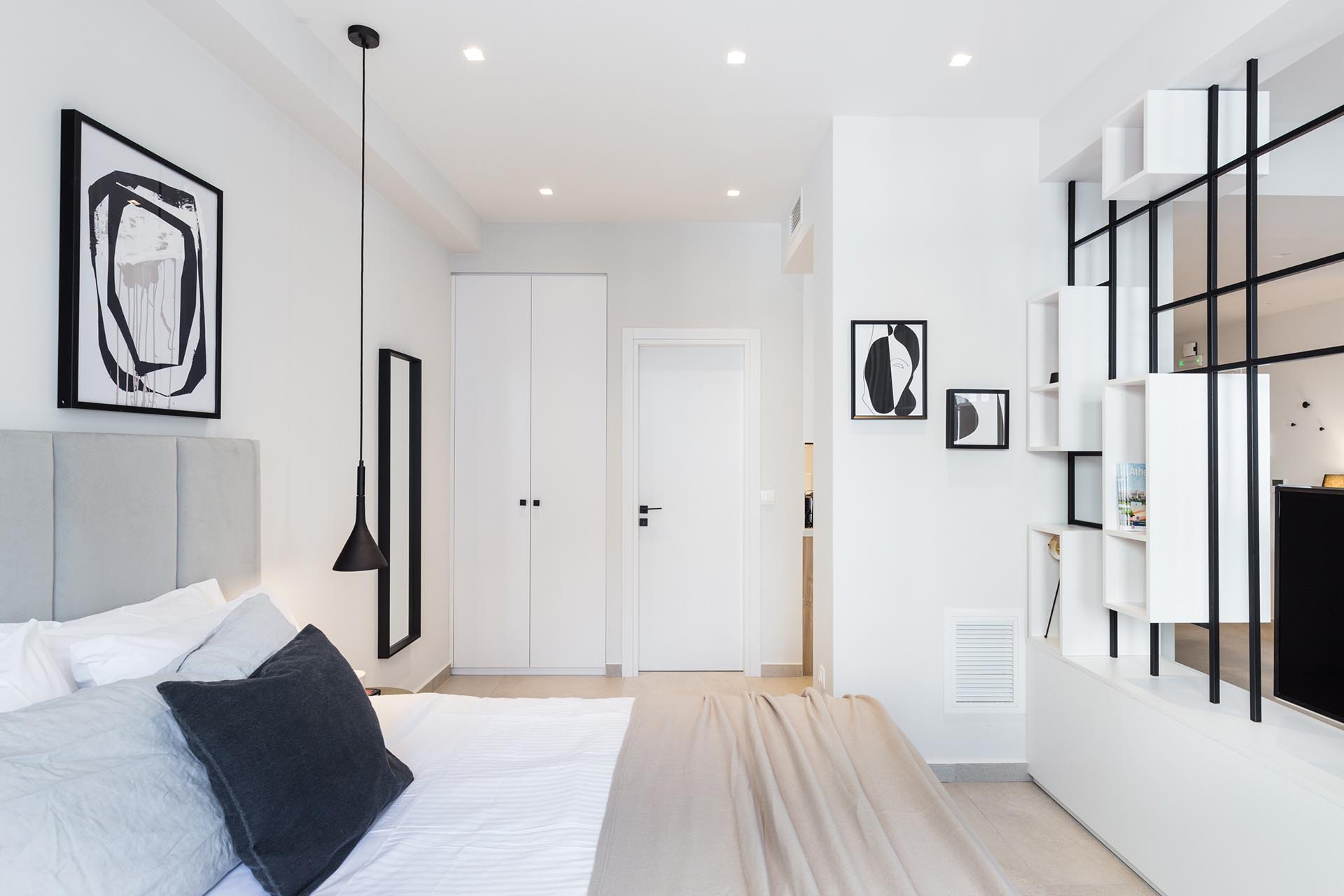 A small and modern bedroom with an open room divider to the living room.