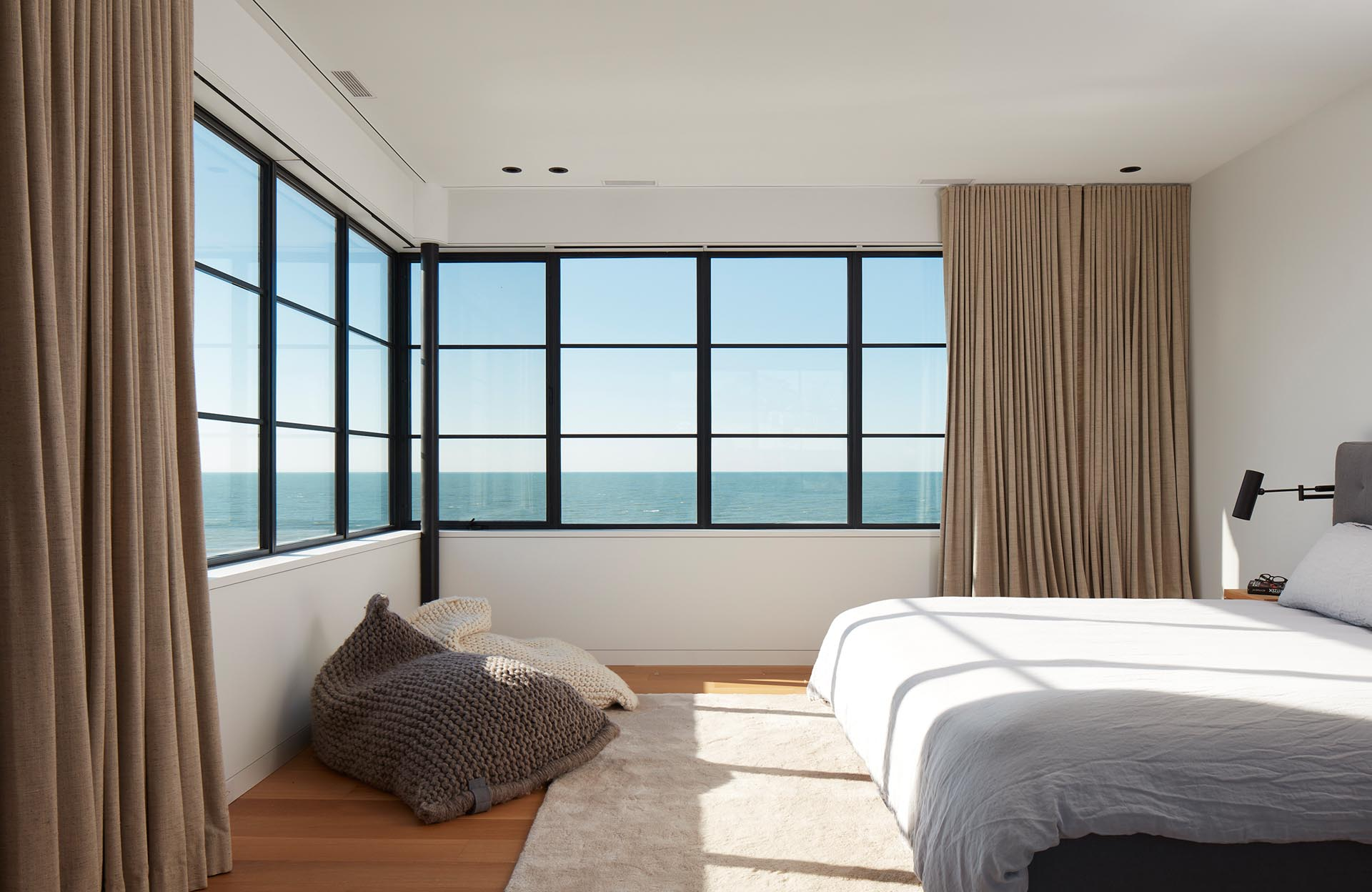In this modern bedroom, the black-framed windows wrap around the corner of the bedroom, flooding the room with natural light during the day.
