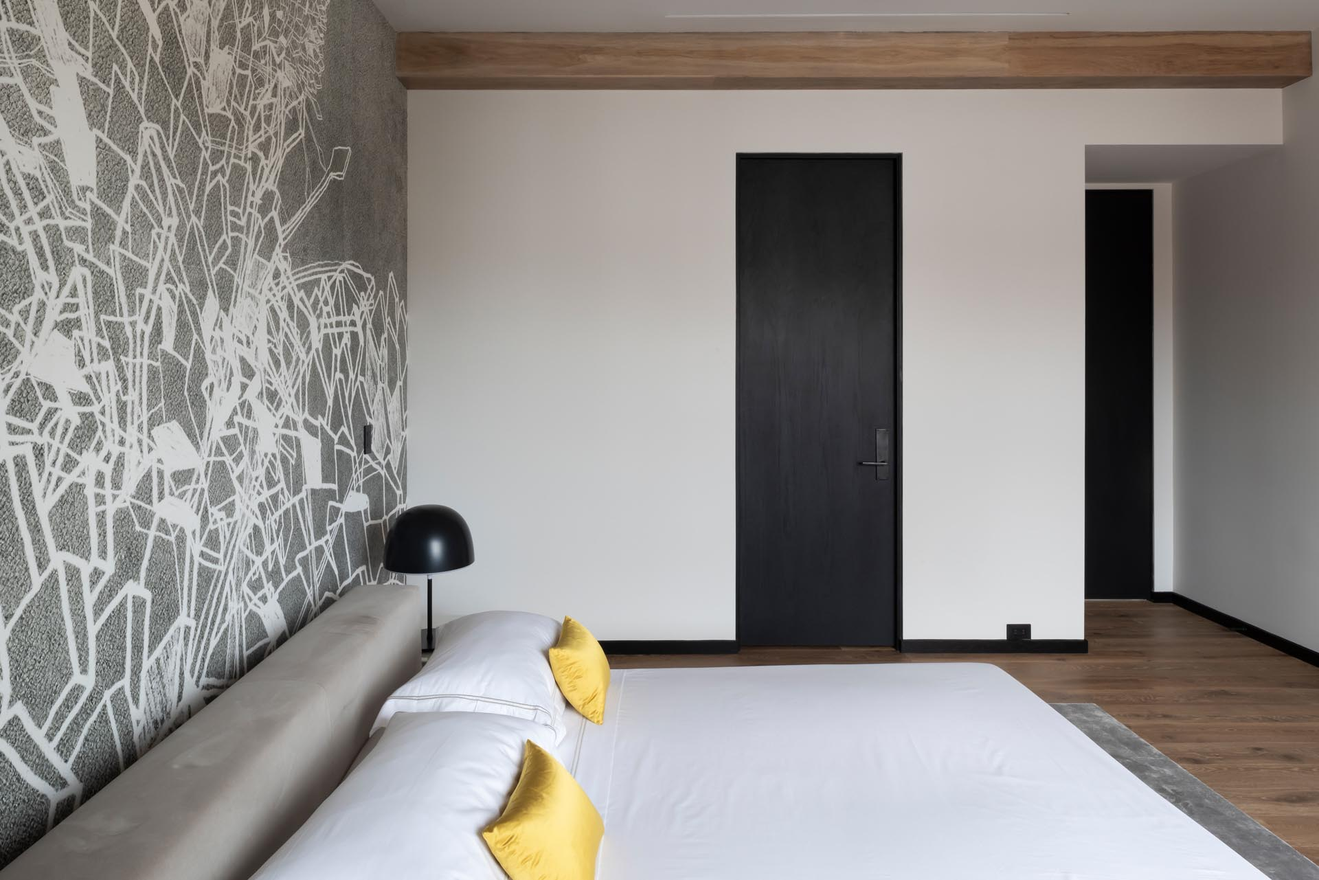 A modern bedroom with a gray and white geometric wallpaper.