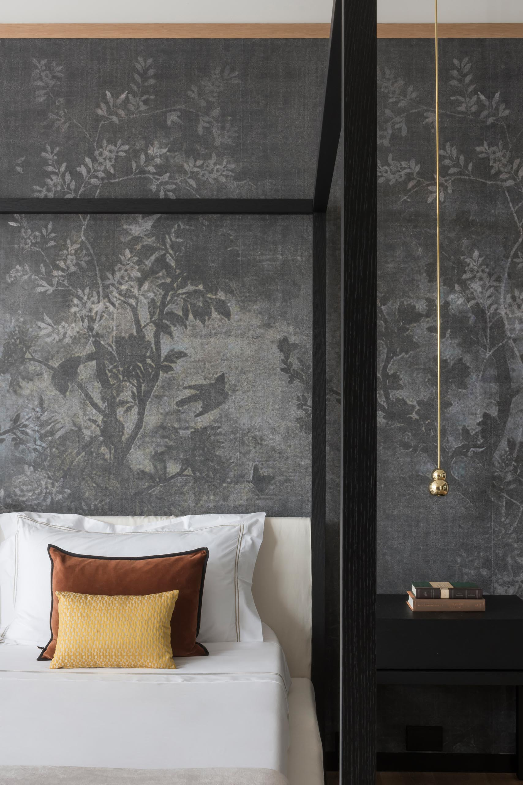 A modern bedroom with a wallpaper that features a floral print.
