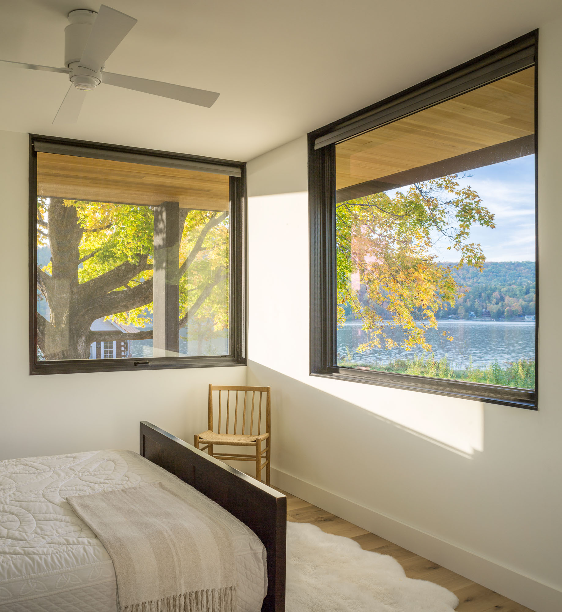 In this modern bedroom, black framed windows on two walls look out to the lake and trees.