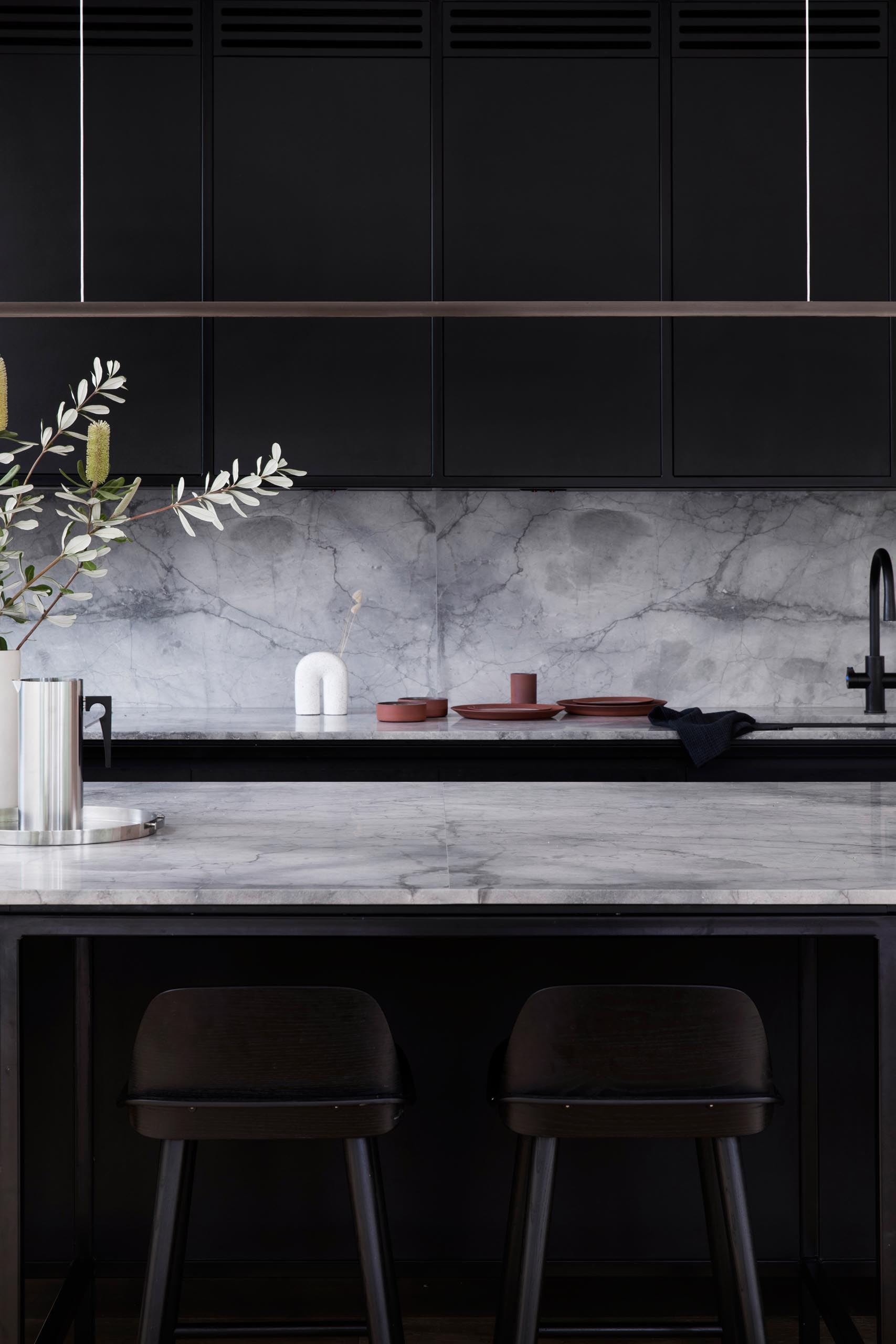 A modern kitchen has a simple color palette with matte black cabinets that are made from Paperock, a sustainable building material combining condensed layers of renewable paper bonded with resin. Grey marble, black hardware, and a minimalist horizontal light fixture complete the look.