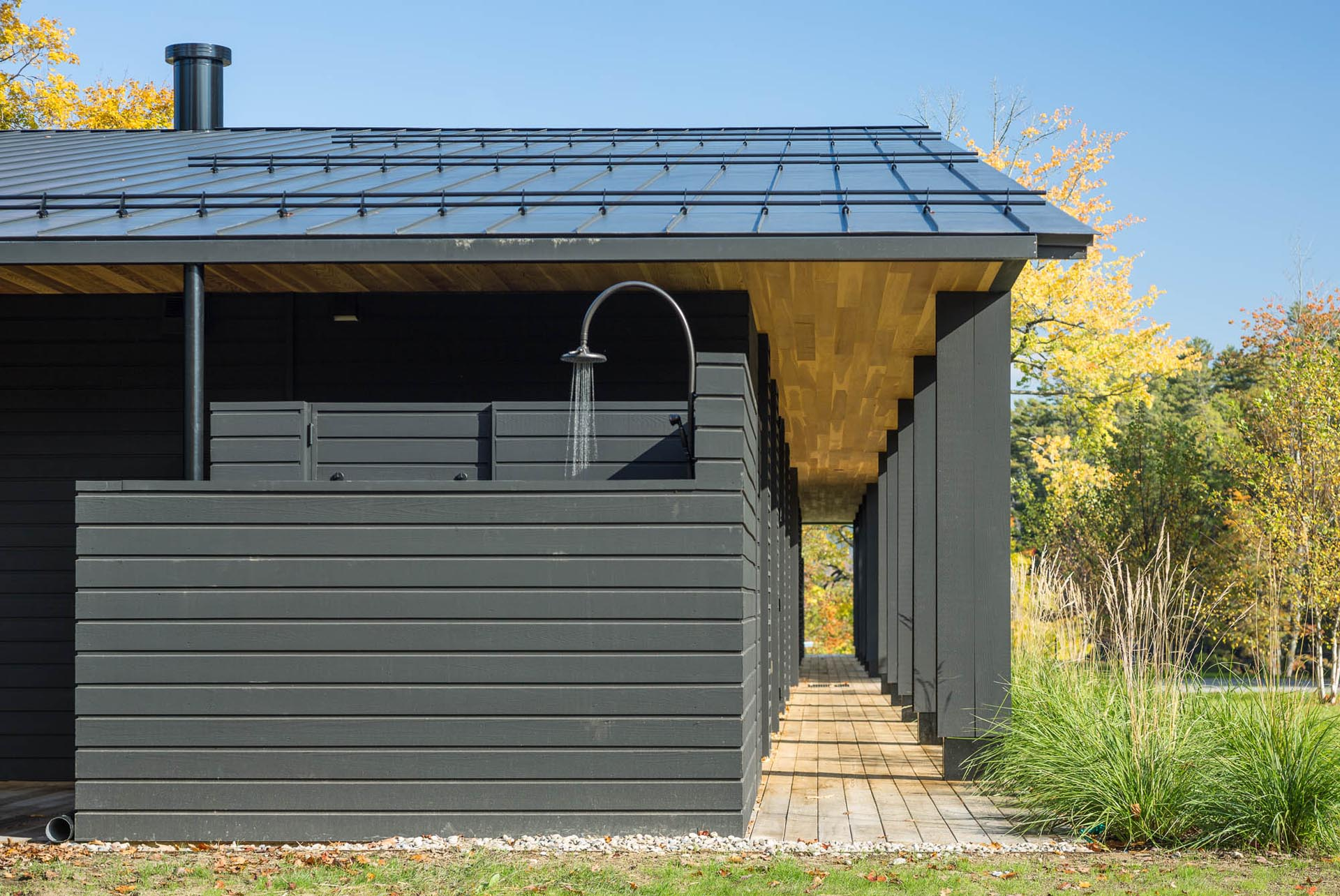 A modern house with black exterior siding, a black metal roof, and an outdoor shower.