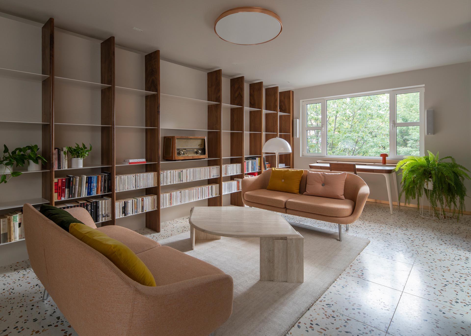 A modern living room with terrazzo tile floors, and a custom wood and metal bookshelf.