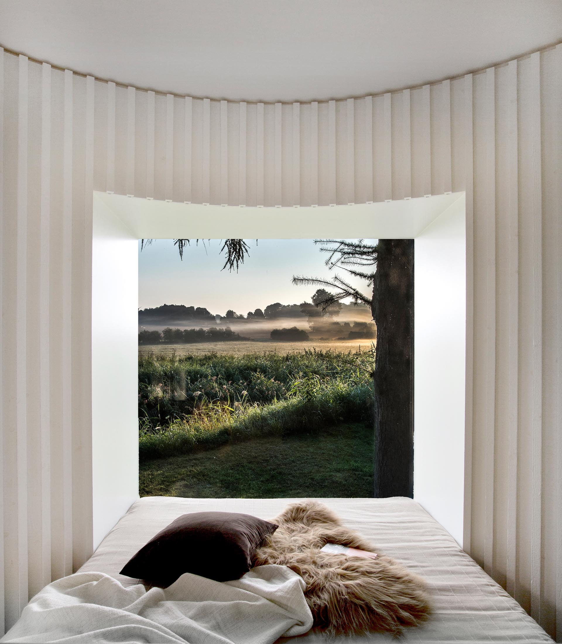 In this curved bedroom, a desk is positioned behind the headboard, while at the end of the is a picture window for unobstructed views.