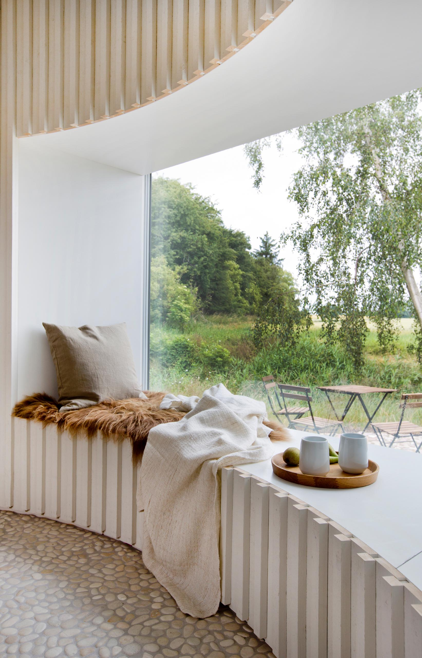 A modern and expansive curved window seat.
