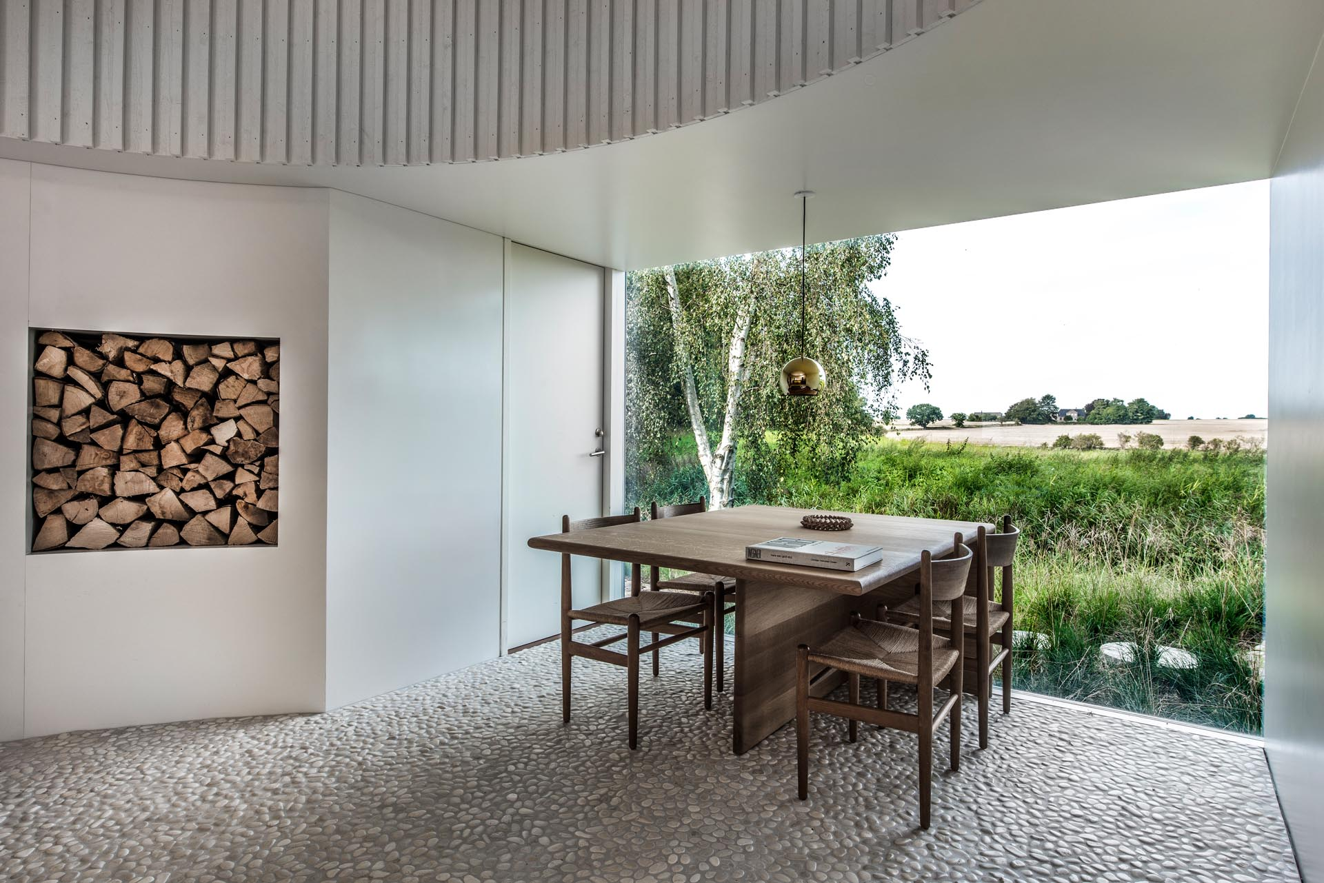 In this modern dining room, the white walls complement the painted board and batten wall cladding, which are included to provide a calm backdrop for the constantly changing textures and colors of the agricultural landscape seen through the window.