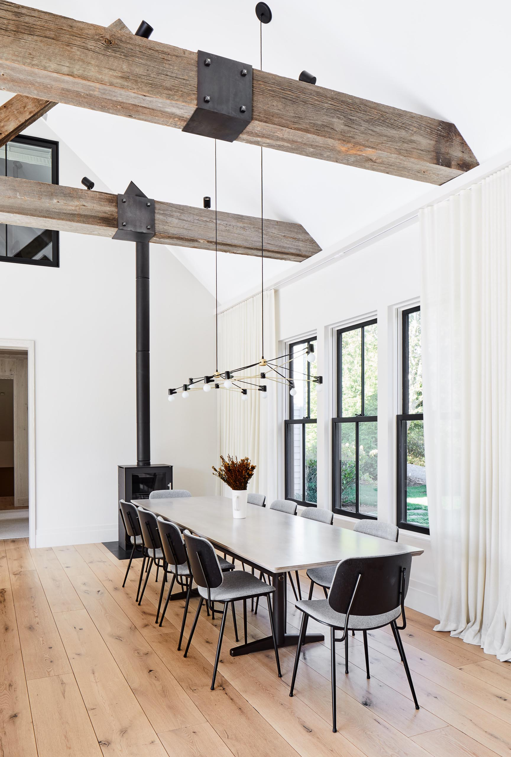 This modern farmhouse dining room features the Double Cord Chandelier from Brendan Ravenhill Studio, which extends over the large dining table. Throughout the home there's solid wide plank white oak from The Hudson Company with a clear Bona Traffic finish.
