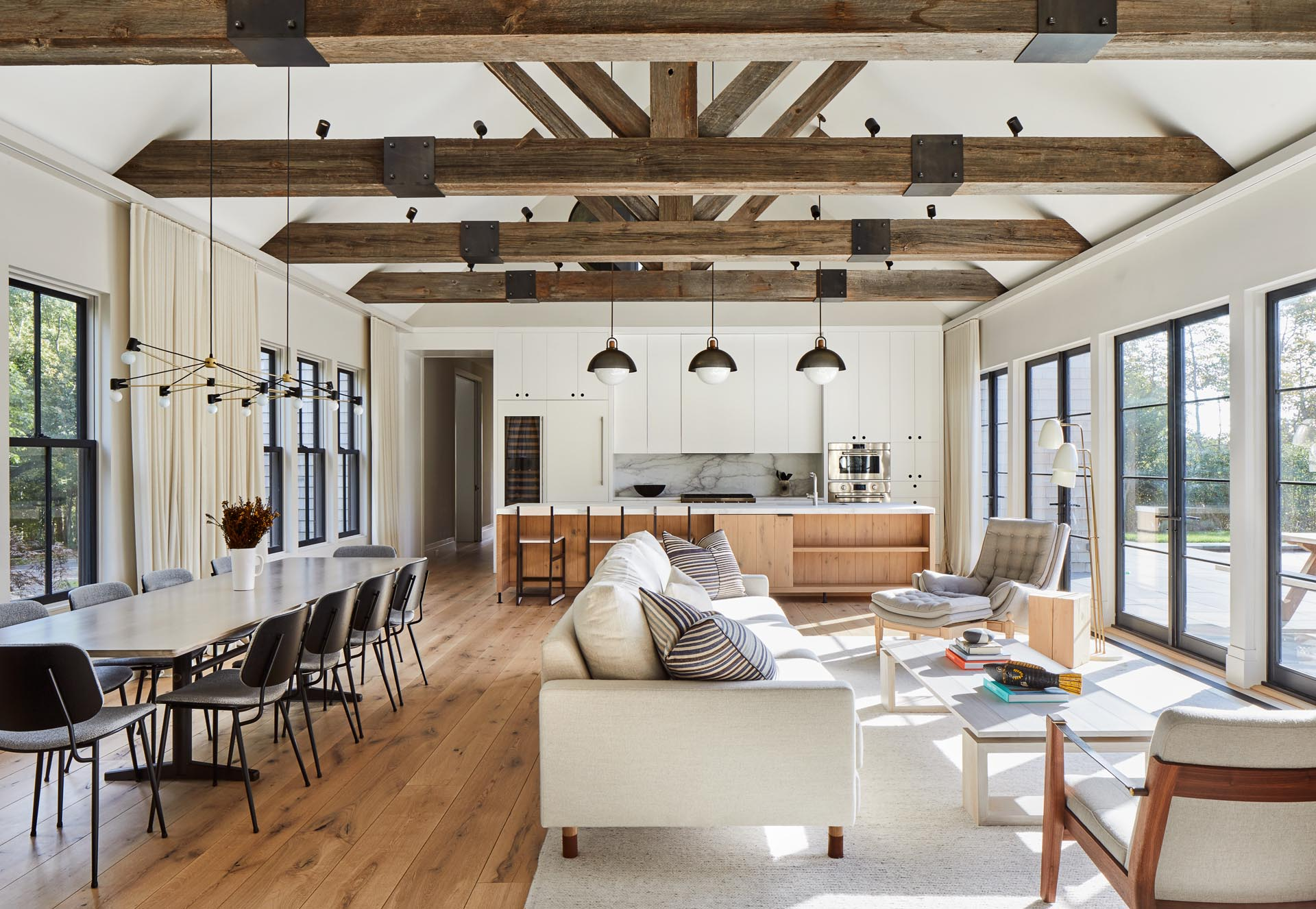 This modern farmhouse great room has plenty of room for the living room, dining area, and kitchen, with exposed beams, and windows on one side, and doors on the other.
