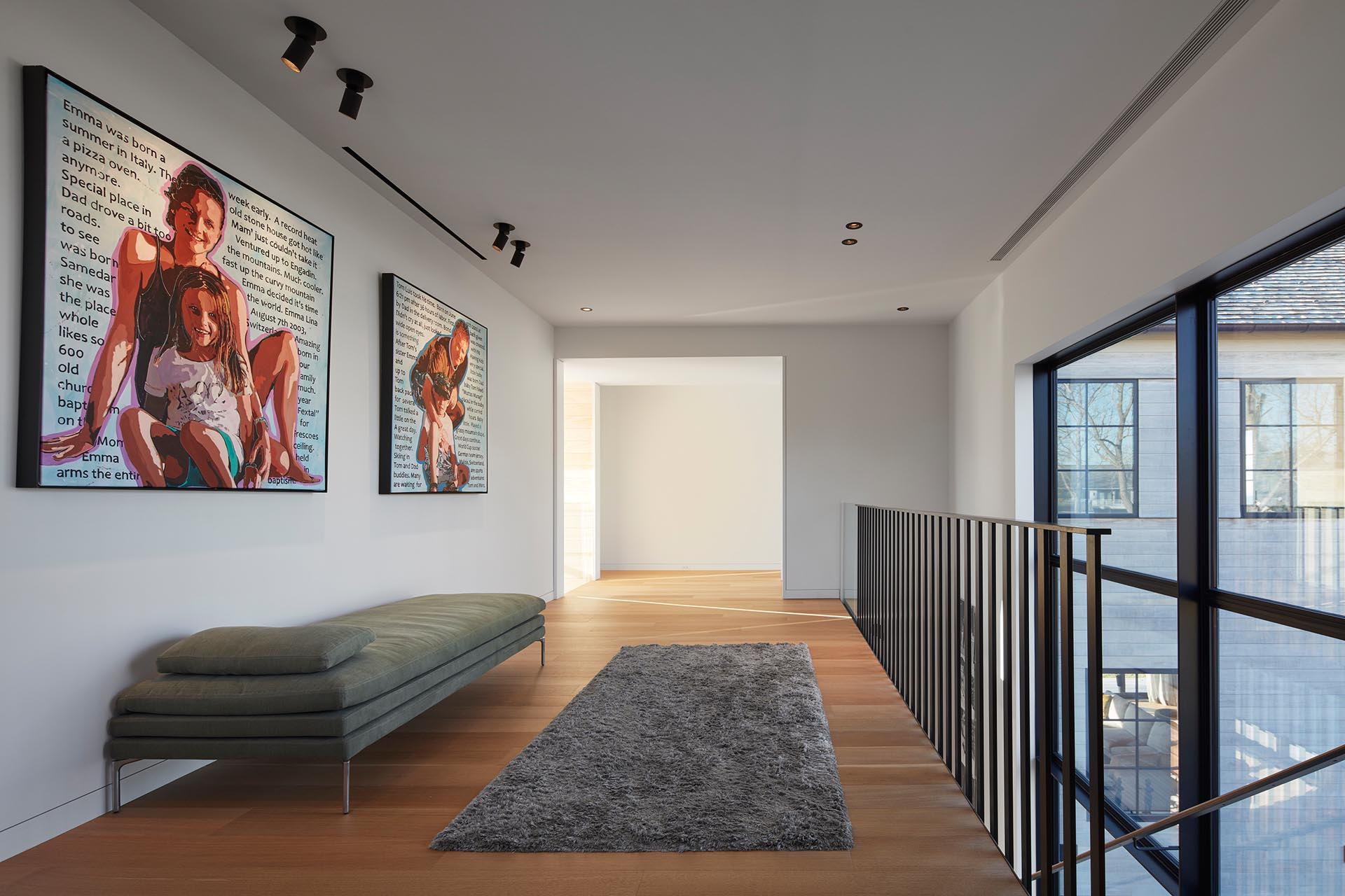 At the top of the stairs in this modern house, there's an open hallway with a seating area that connects to the bedrooms and bathrooms.