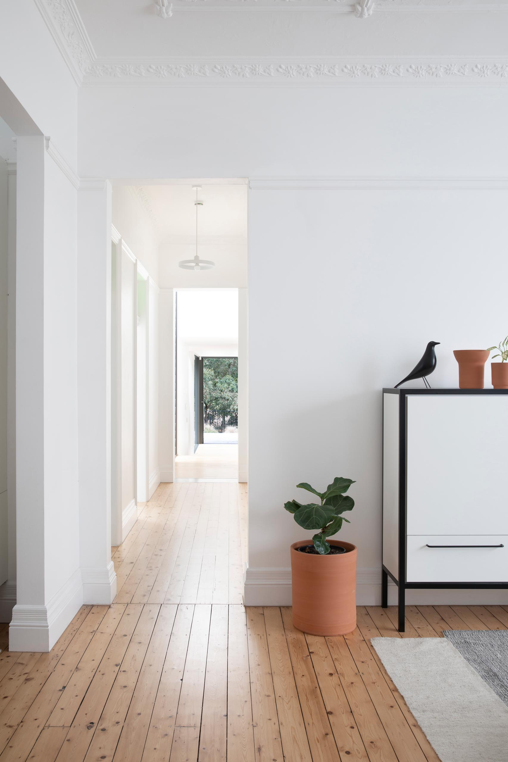 Wood floors can be found throughout the home, while white walls draw focus to era-defining hallmarks like ornate pressed-tin ceilings and cast-iron fireplaces, both of which can be seen in a casual living room.