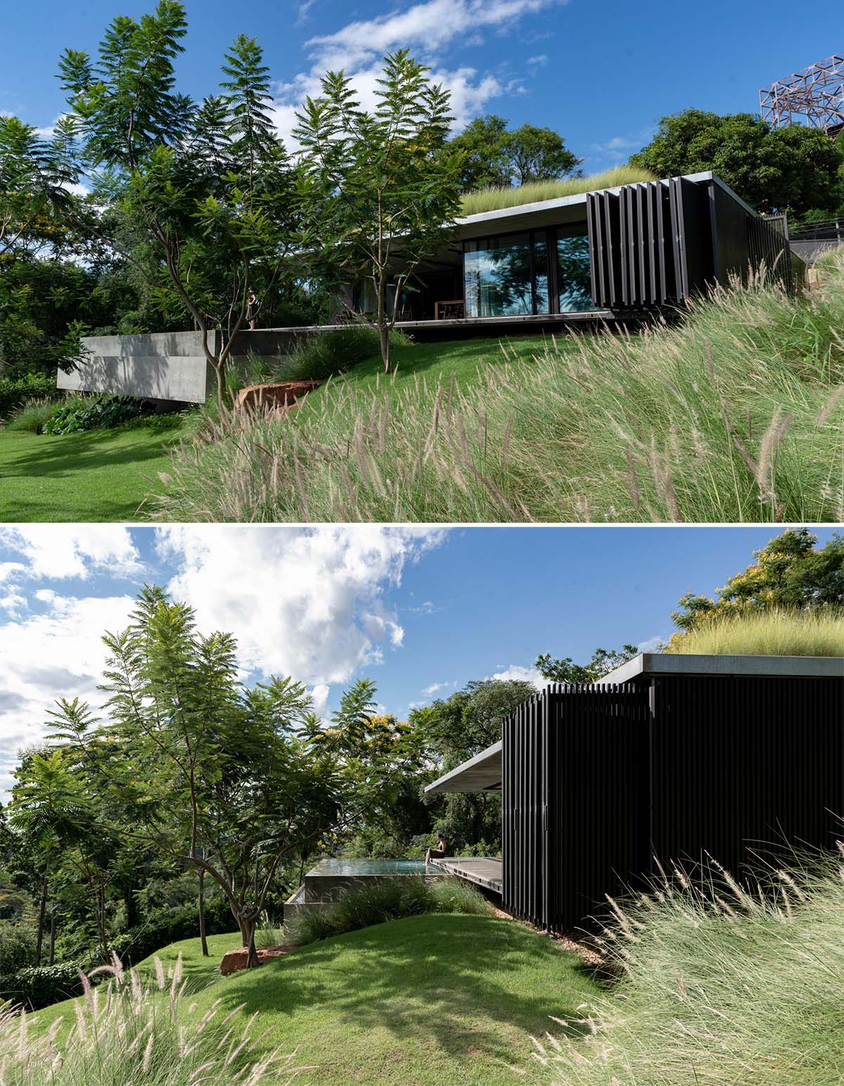 A modern house with a green roof that has folding black screens on its exterior.