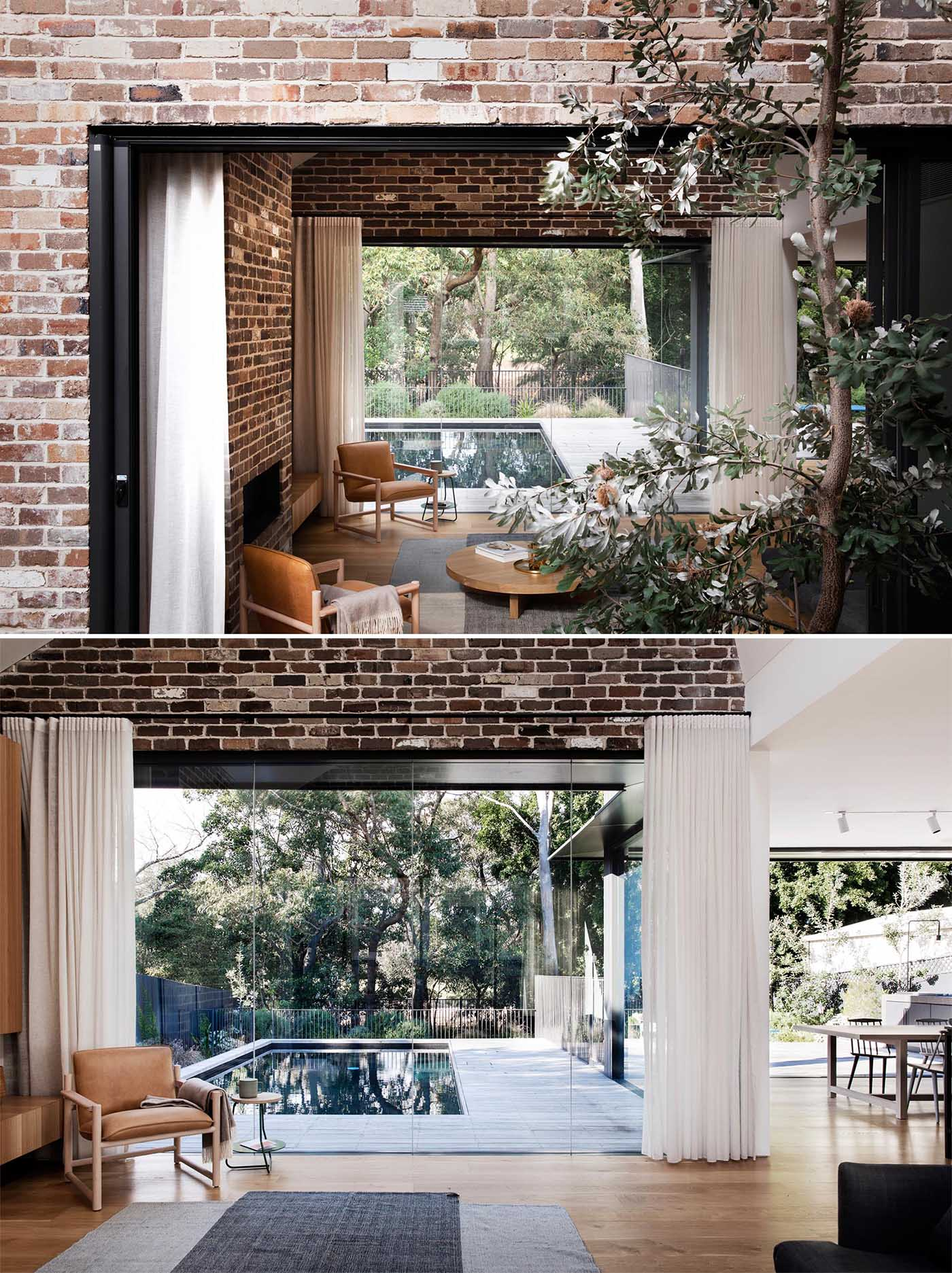 An additional glass wall in living room of a new home new addition provides views of the pool, while the opposite wall opens to a small courtyard with water-wise Australian native plants.