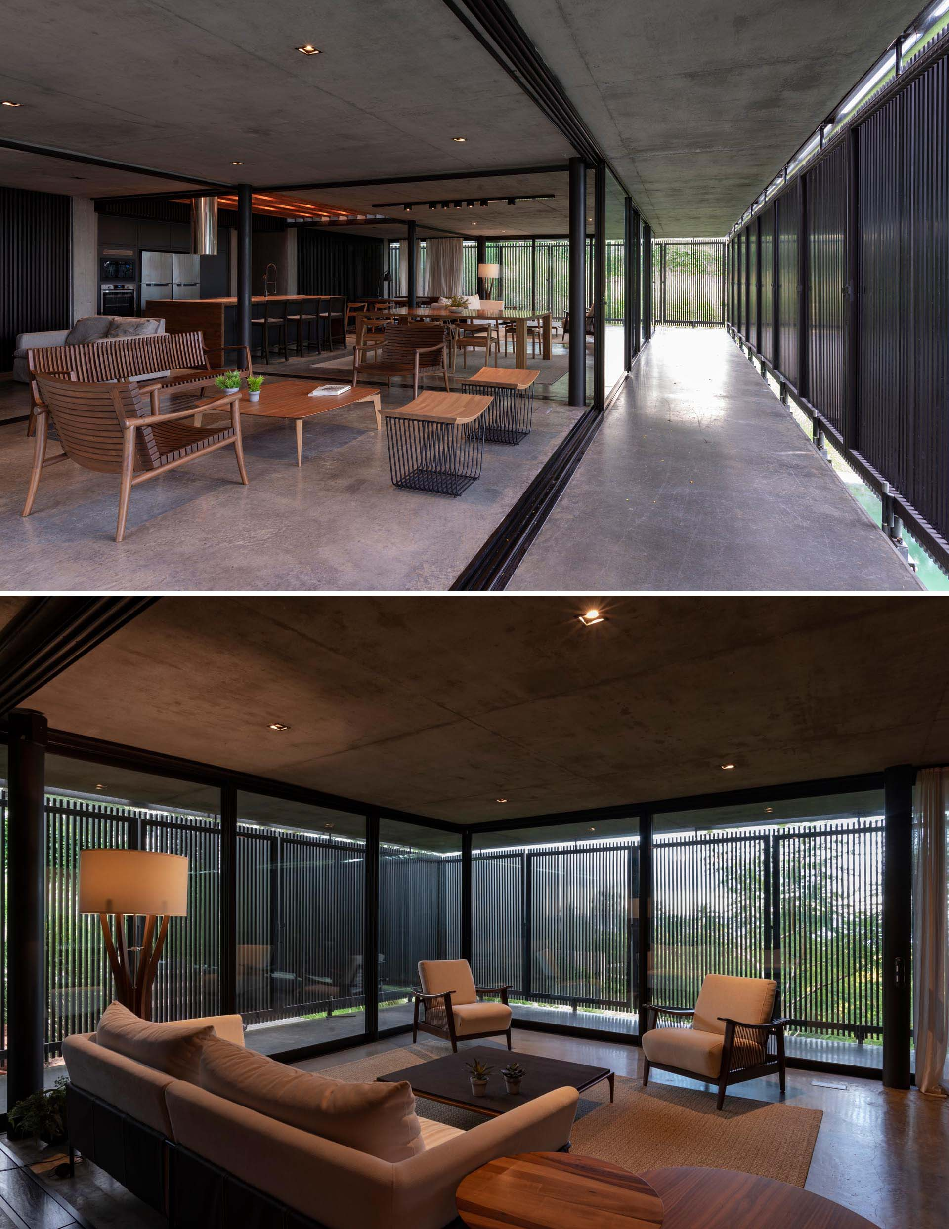 A modern house with an open floor plan, black wood slat screens, glass walls, and concrete floors.