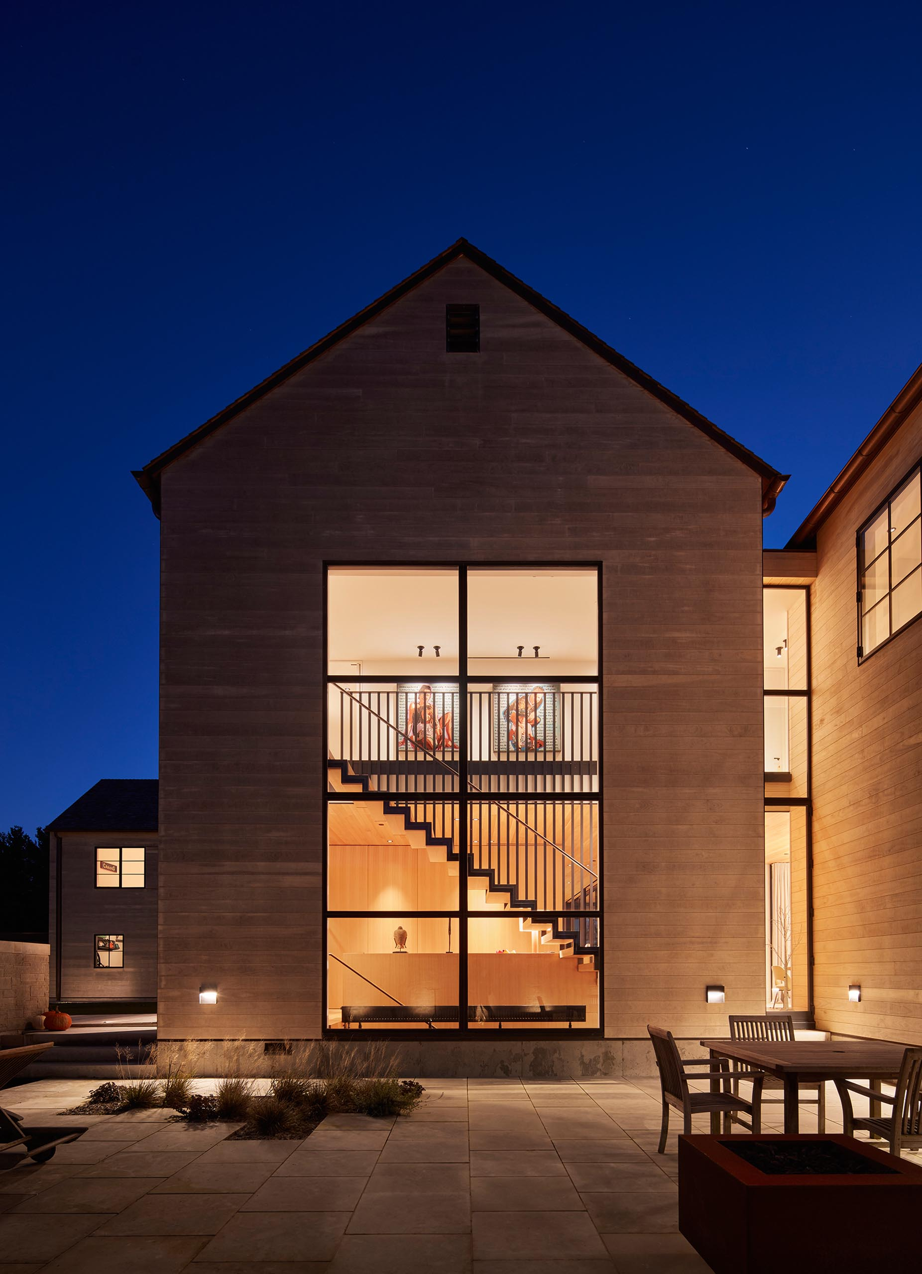 Large windows showcase a steel and wood staircase inside the home.