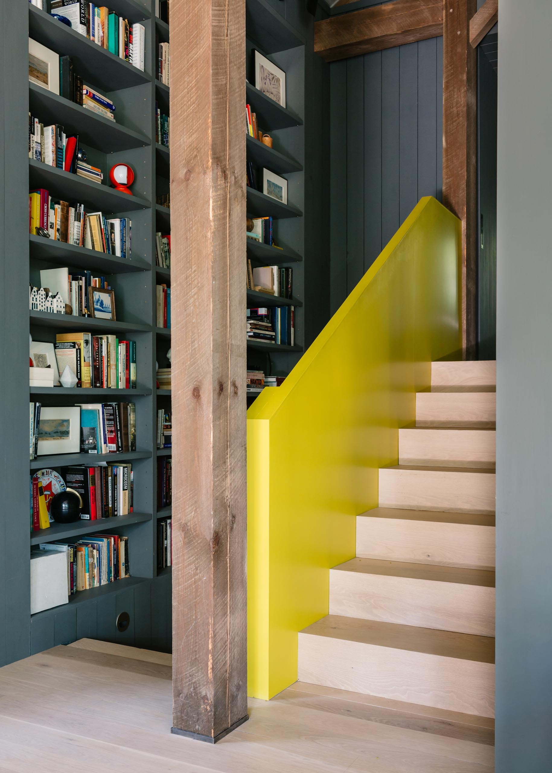 A barn-inspired home with custom bookshelves and a yellow handrail accent.