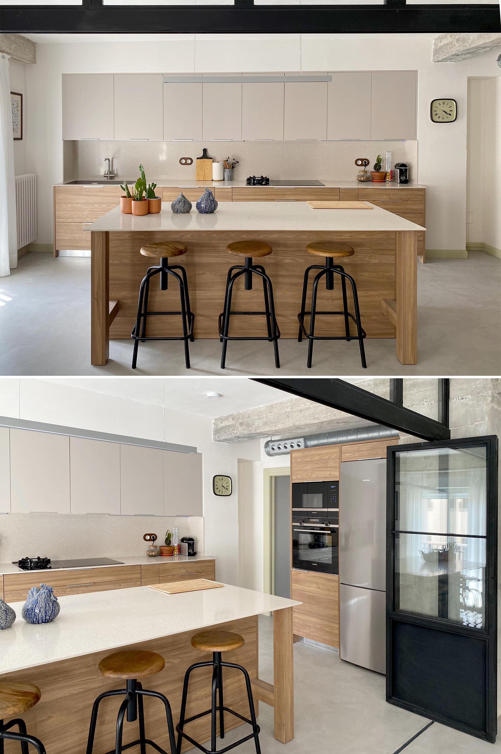 The black framed wall also complements the black stools of the kitchen island, while the kitchen cabinets have a minimalist design.