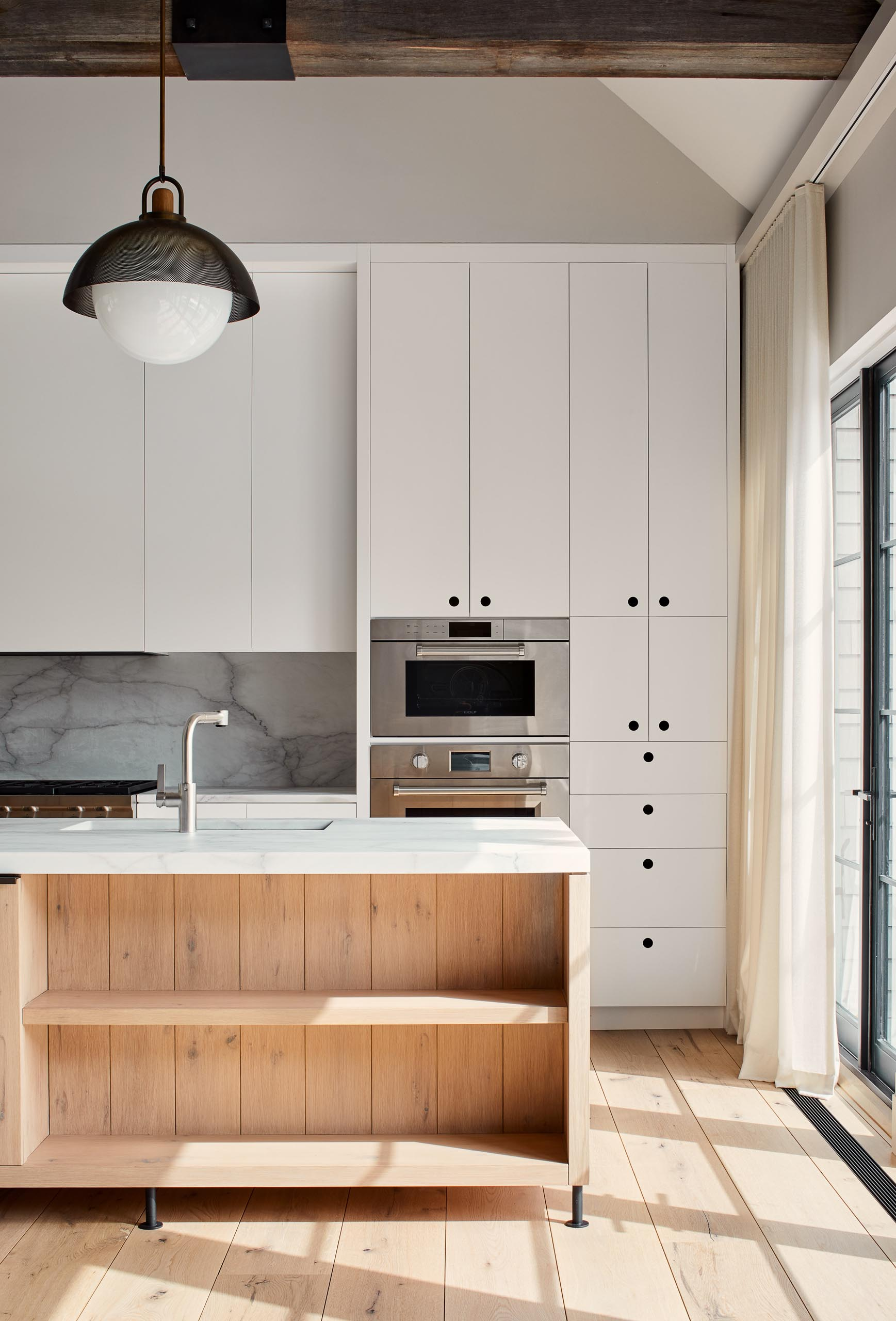 The cabinets in this kitchen are hardware free and include round recessed finger pulls that have been painted black inside.