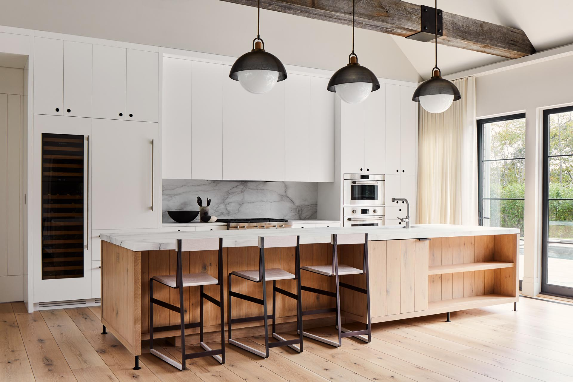 In this modern farmhouse kitchen kitchen, the exhaust fan is concealed within a fixed panel which is flanked by white cabinets. For the cabinets left and right of the stove, the doors hang down below the cabinets so they can be opened by pulling the bottoms of the cabinet doors.