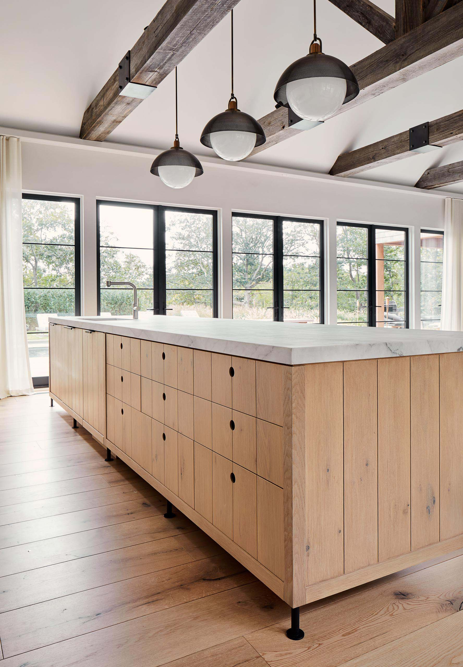 This modern farmhouse kitchen island has wood cabinets and drawers, while hanging above the island are pendant lights from Allied Maker, and the stools are from Skram Furniture Co.