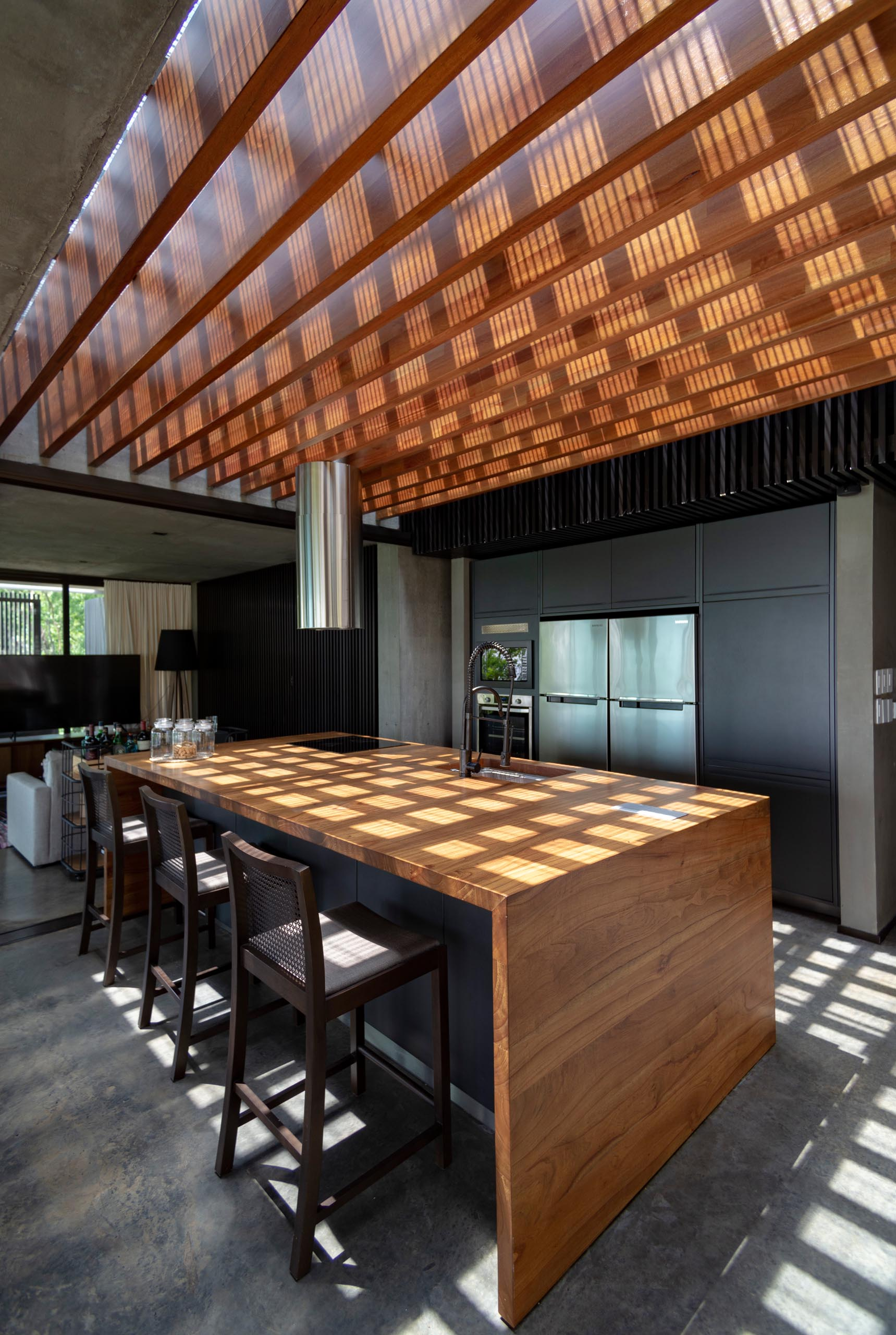 A modern kitchen with minimalist black cabinets and an oversized wood island.
