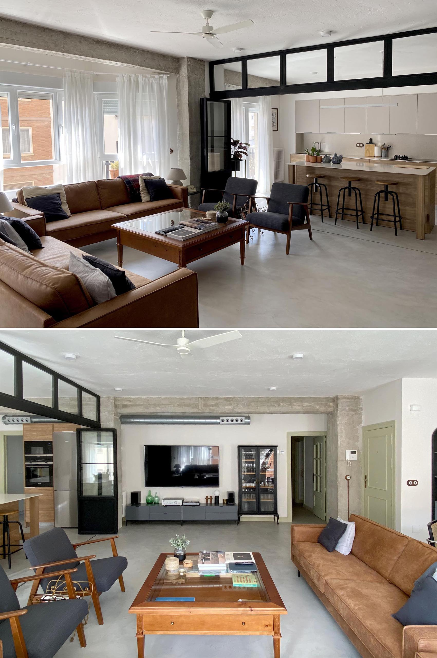 This modern living room showcases the concrete flooring, and is furnished with leather couches, a pair of armchairs, and a wood coffee table. On the living room wall, there's a low console and glass front cabinet that complements the black framed doors.