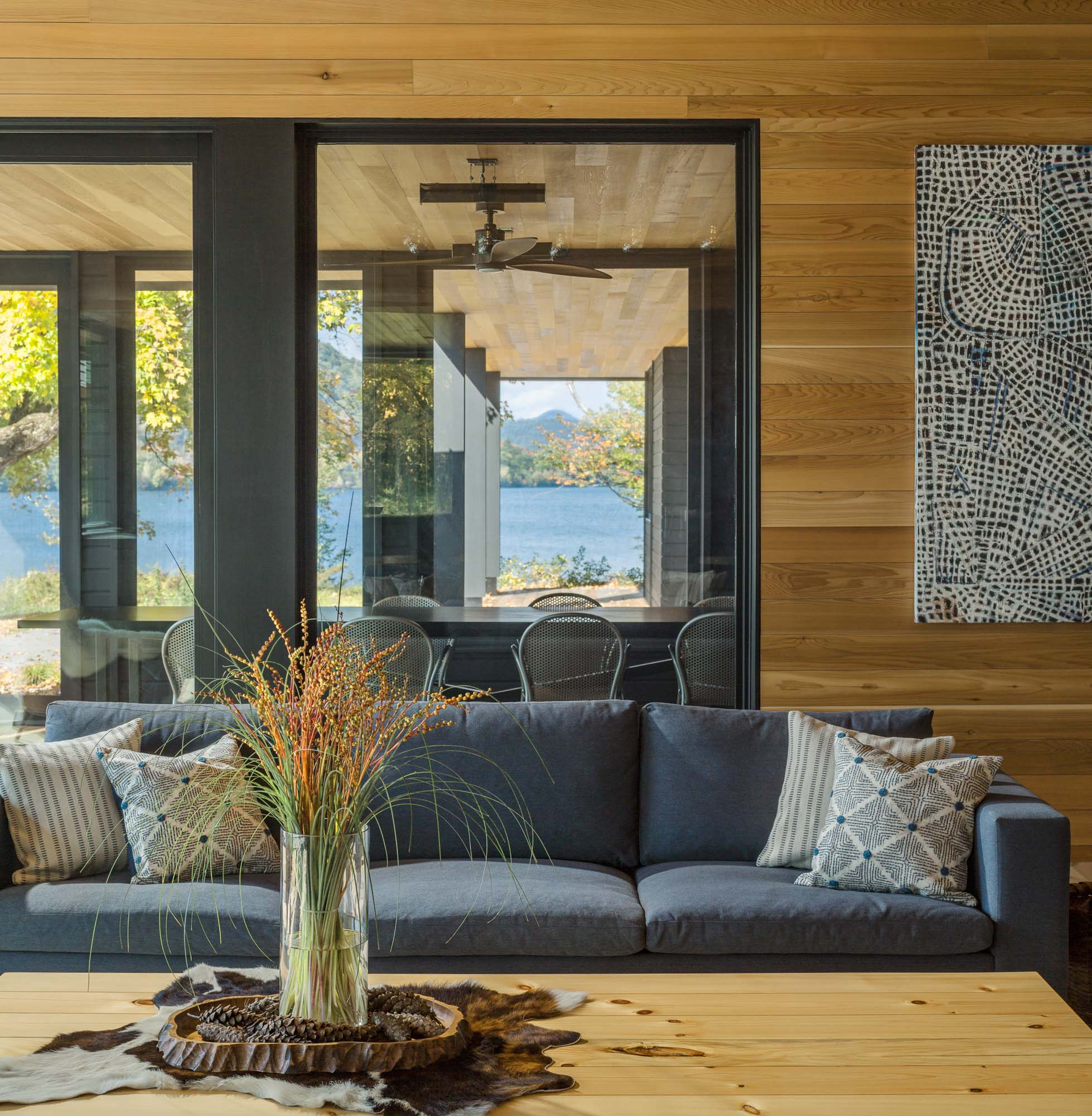 A modern lakeside home with a living room and nearby dining table.
