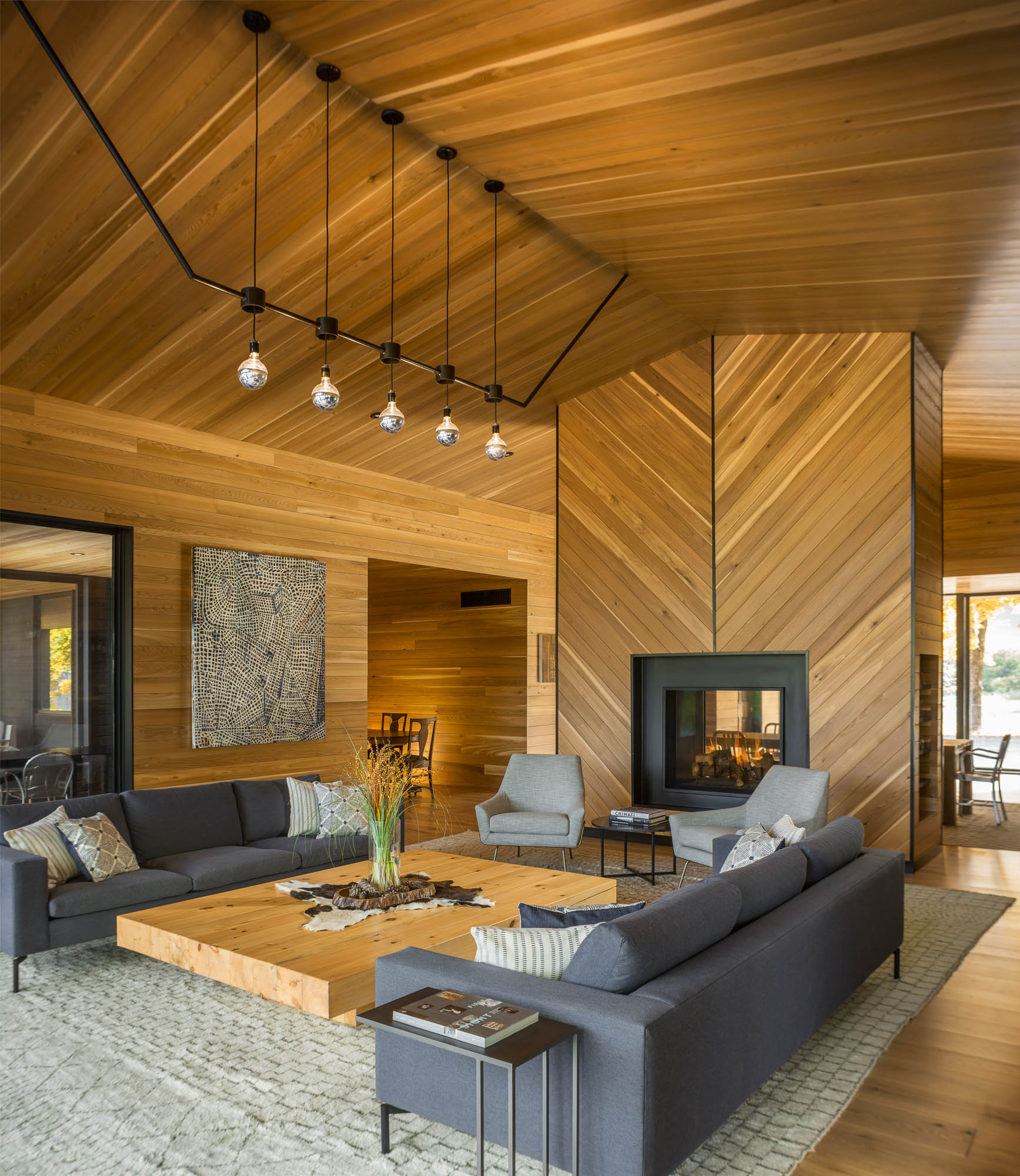 A modern living room with a glass front fireplace, a large coffee wood coffee table, a unique lighting element, and wood-lined walls and ceiling.
