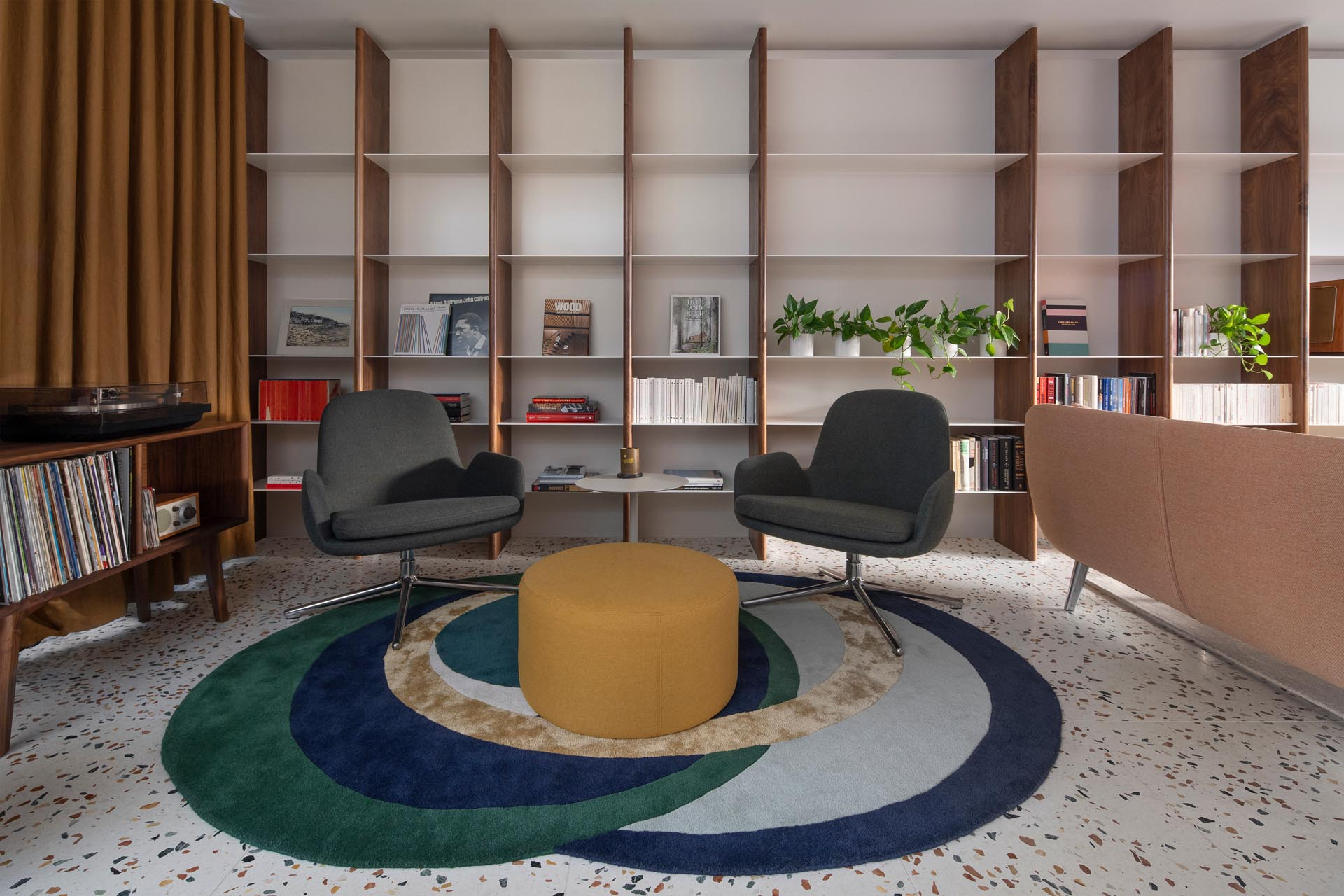 This modern living room with a terrazzo tiled floor, receives plenty of natural light, while a custom wood and metal shelving unit covers the entire wall and expands through to a secondary seating area with a colorful rug and record player.