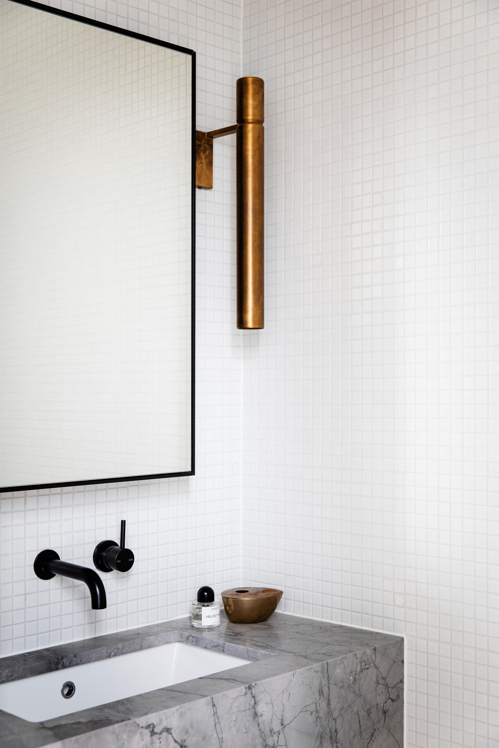This powder room also includes the small square tiles, however a gray stone vanity and black mirror frame add a contrasting element, and a brass light fixture adds a metallic accent.