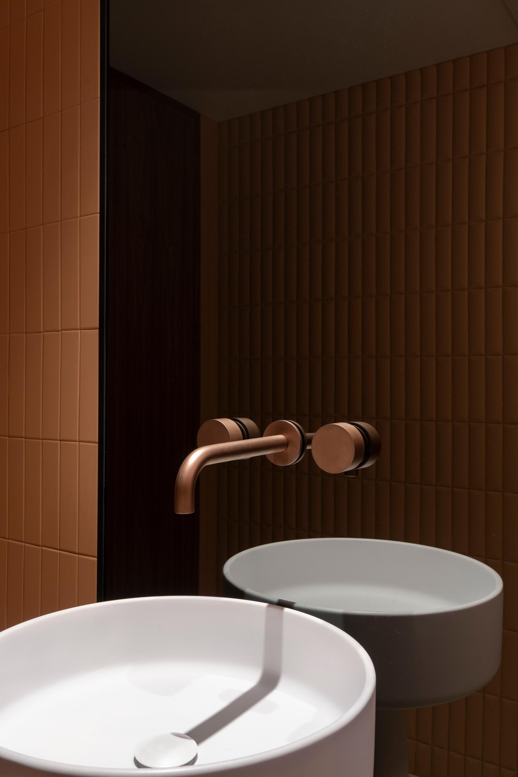 This modern powder room features smoked glass, copper faucets, Italian pedestal washbasin, and terracotta ceramics reminiscent of upholstered leather create a chic appearance.