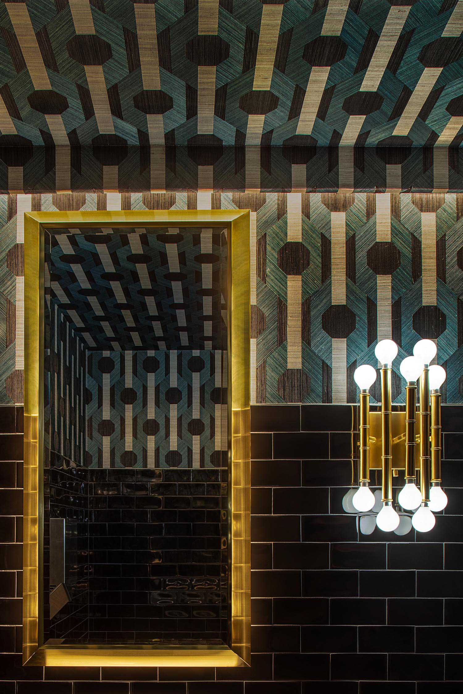Patterned walls and black subway tiles in a restaurant bathroom.