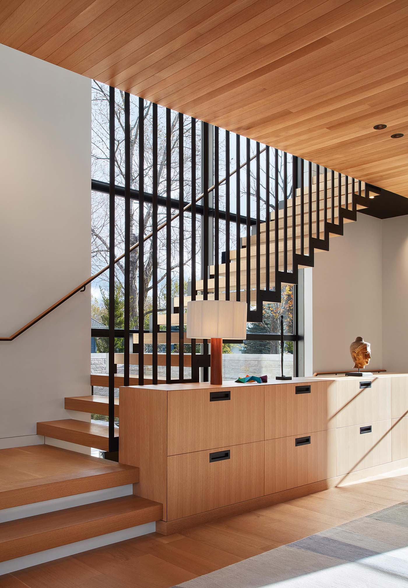 A suspended steel staircase with white oak treads connects the different levels of the home, while built-in cabinetry adds an element of storage.
