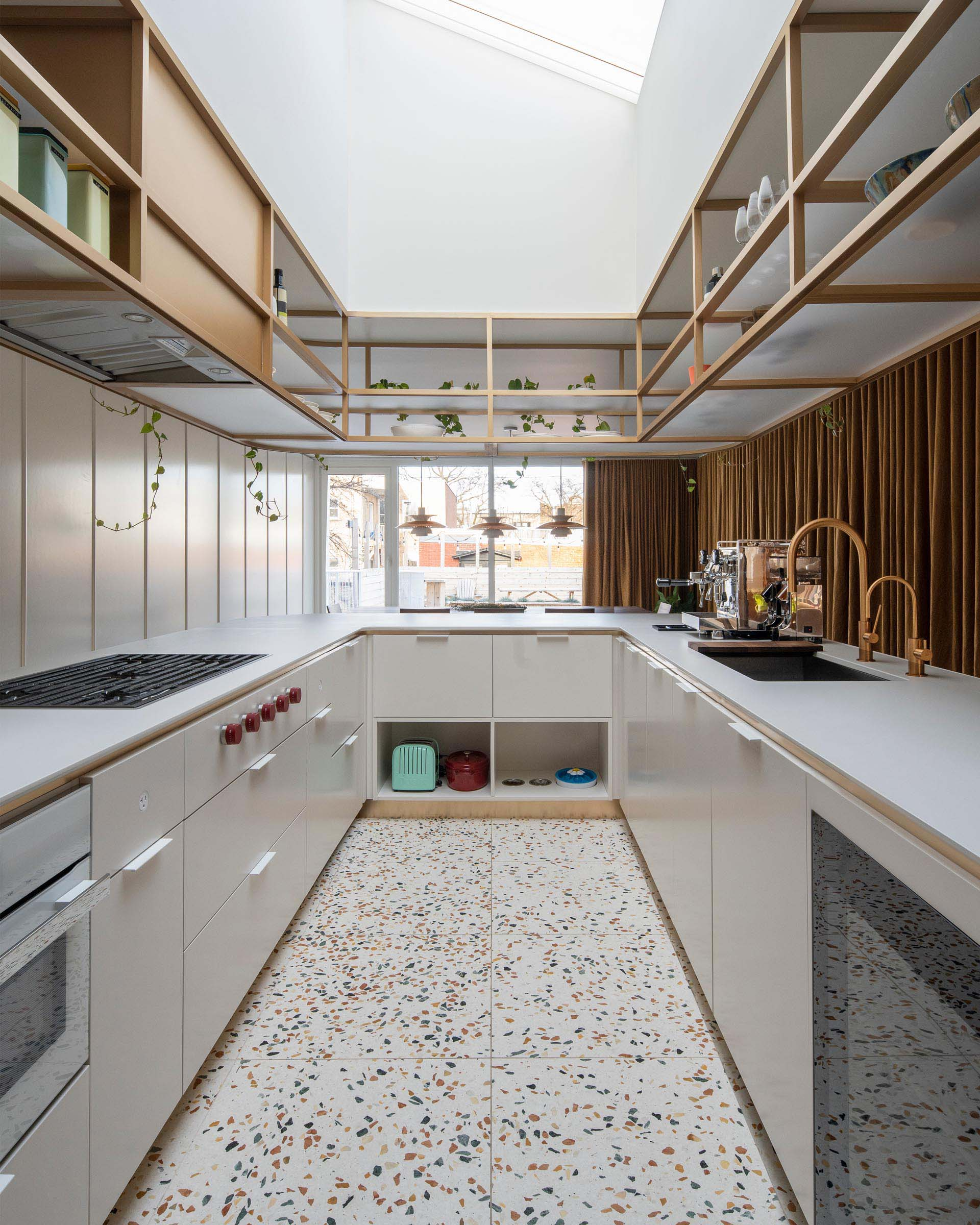 This modern U-shaped kitchen has a terrazzo tile floor, and an elegantly curved countertop with matching upper shelves that are open for easy access.