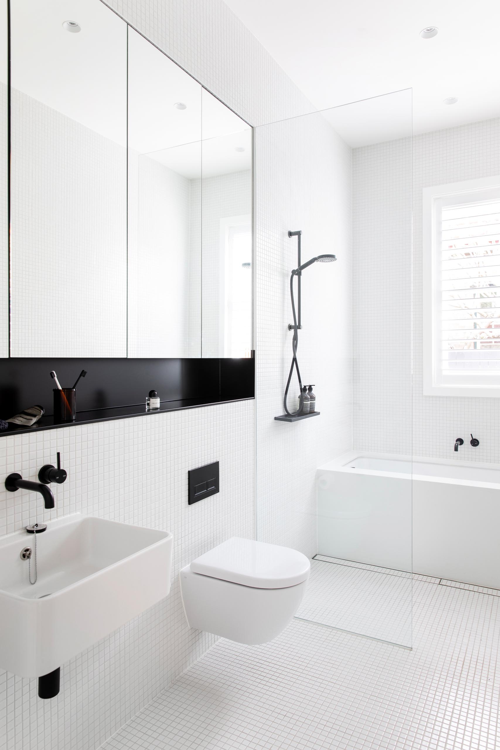 This modern bathroom has a simple white design with black accents. There's small white square tiles covering the walls and floor, a built-in bathtub, and a mirror with a recessed black shelf below. In addition to the window above the bath, there's also a skylight to add natural light to the space.