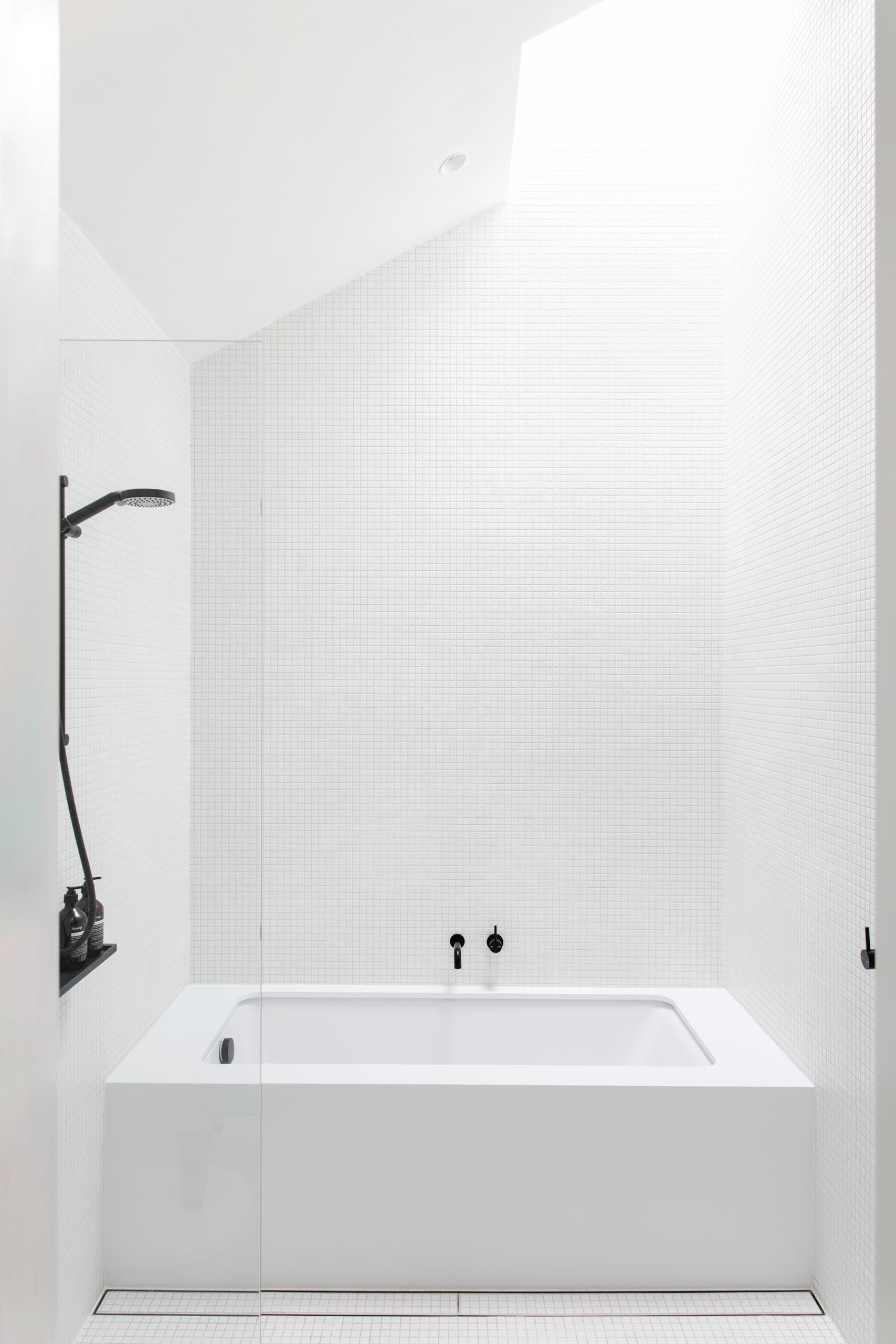 A white bathroom with black hardware accents features small square tiles, a built-in bathtub, and a skylight.