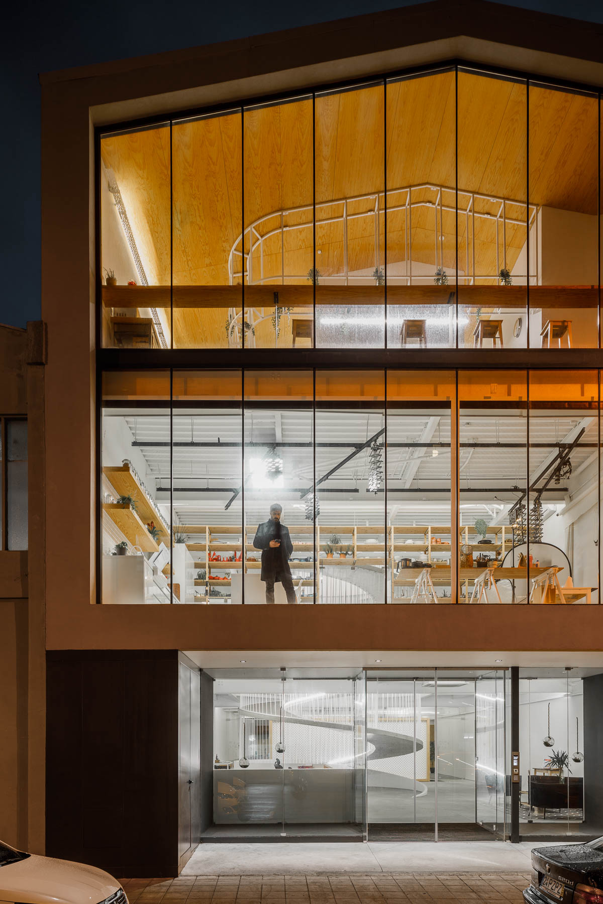 The exterior of this modern office has walls of glass providing a glimpse of the interior for the pedestrians on the street.