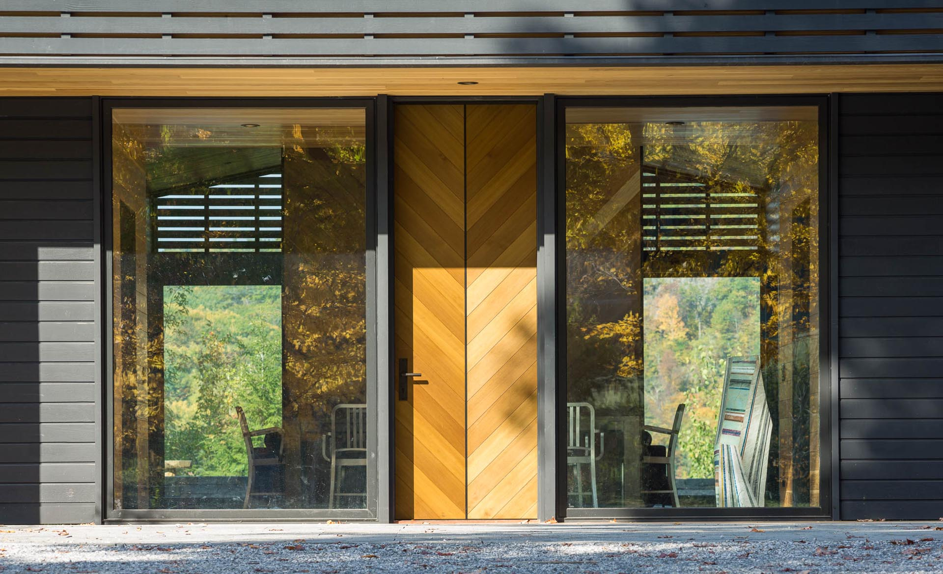 An oversized front door is flanked by two large floor-to-ceiling windows.