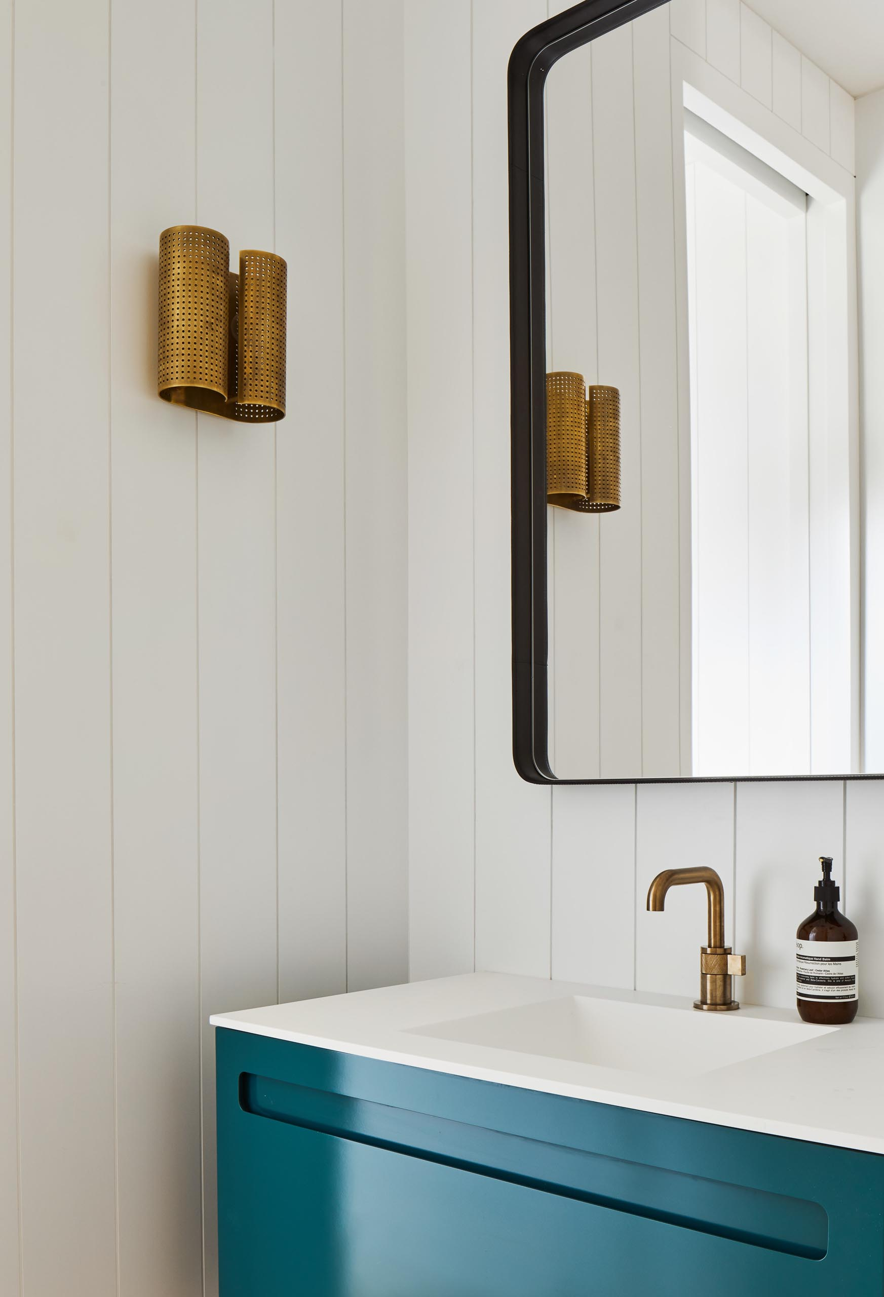 This powder room showcases a pop of color in the form of a bright blue vanity from A&F Supply in NYC, which is accented by Brizo faucet and a Kelly Wearstler sconce.