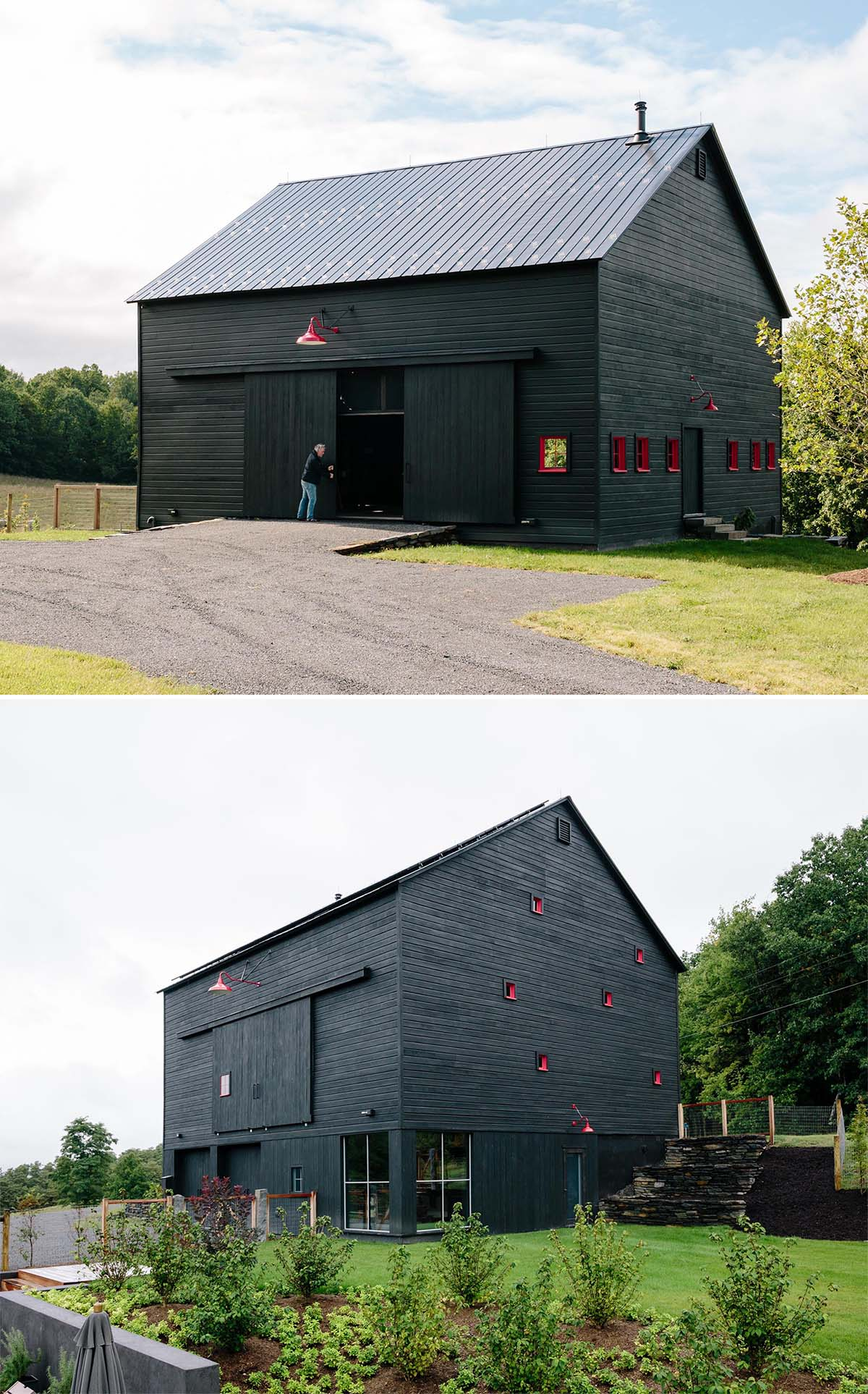 A modern black barn with solar panels and red window frames.