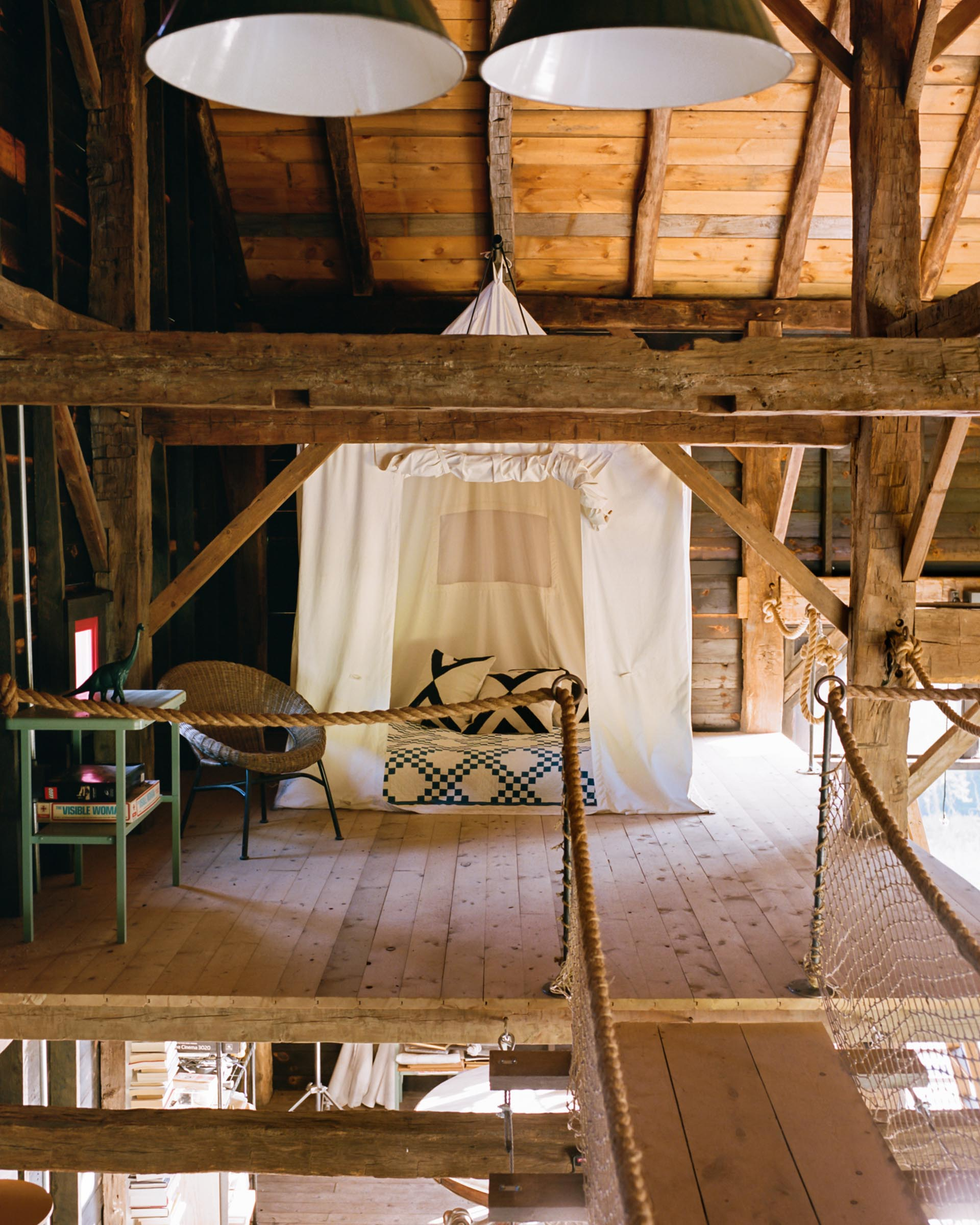 A barn interior with a bed surrounded by a fabric tent.