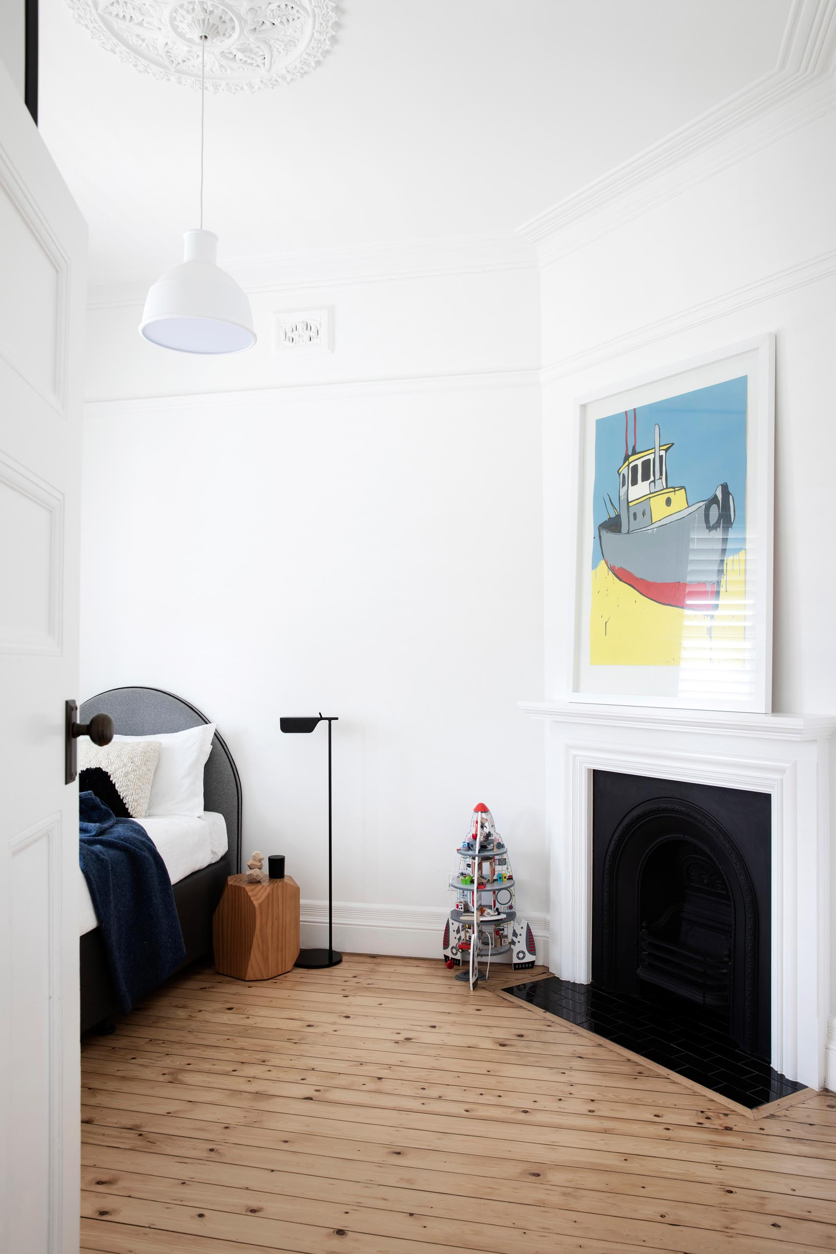 A cast-iron fireplace in this updated bedroom is a throw back to the original design of the house.