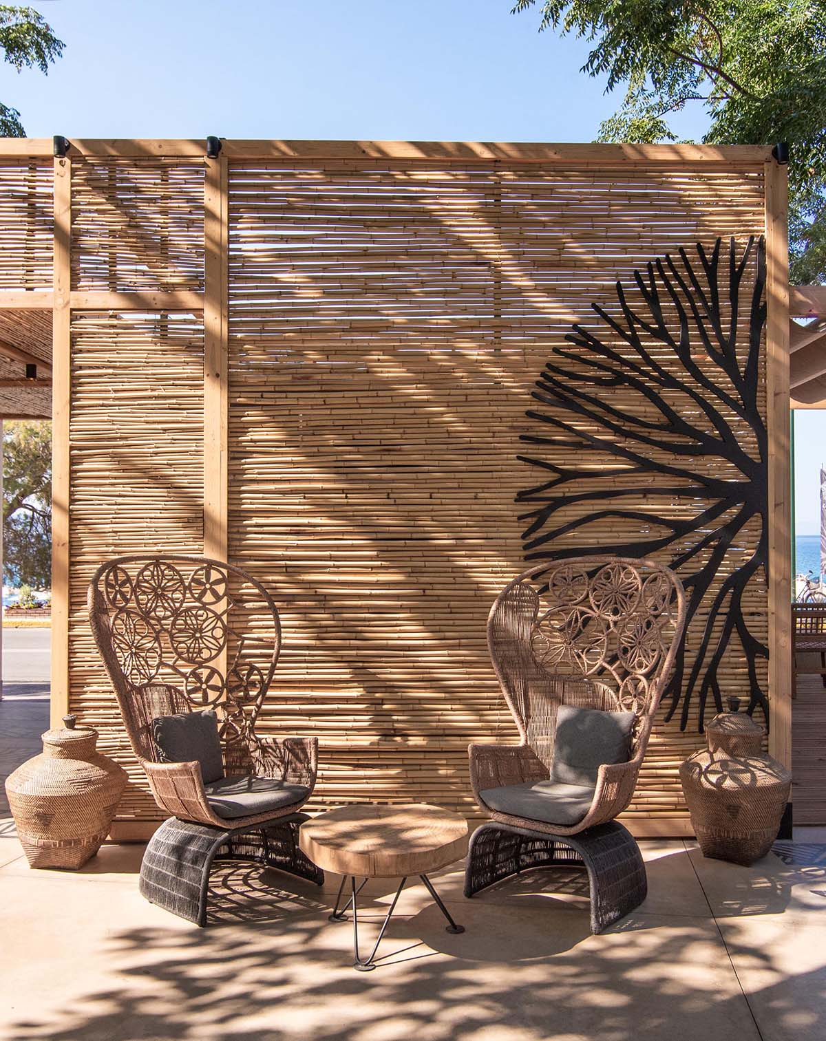 A modern outdoor restaurant with reed screens that provide shade and create a beach aesthetic.