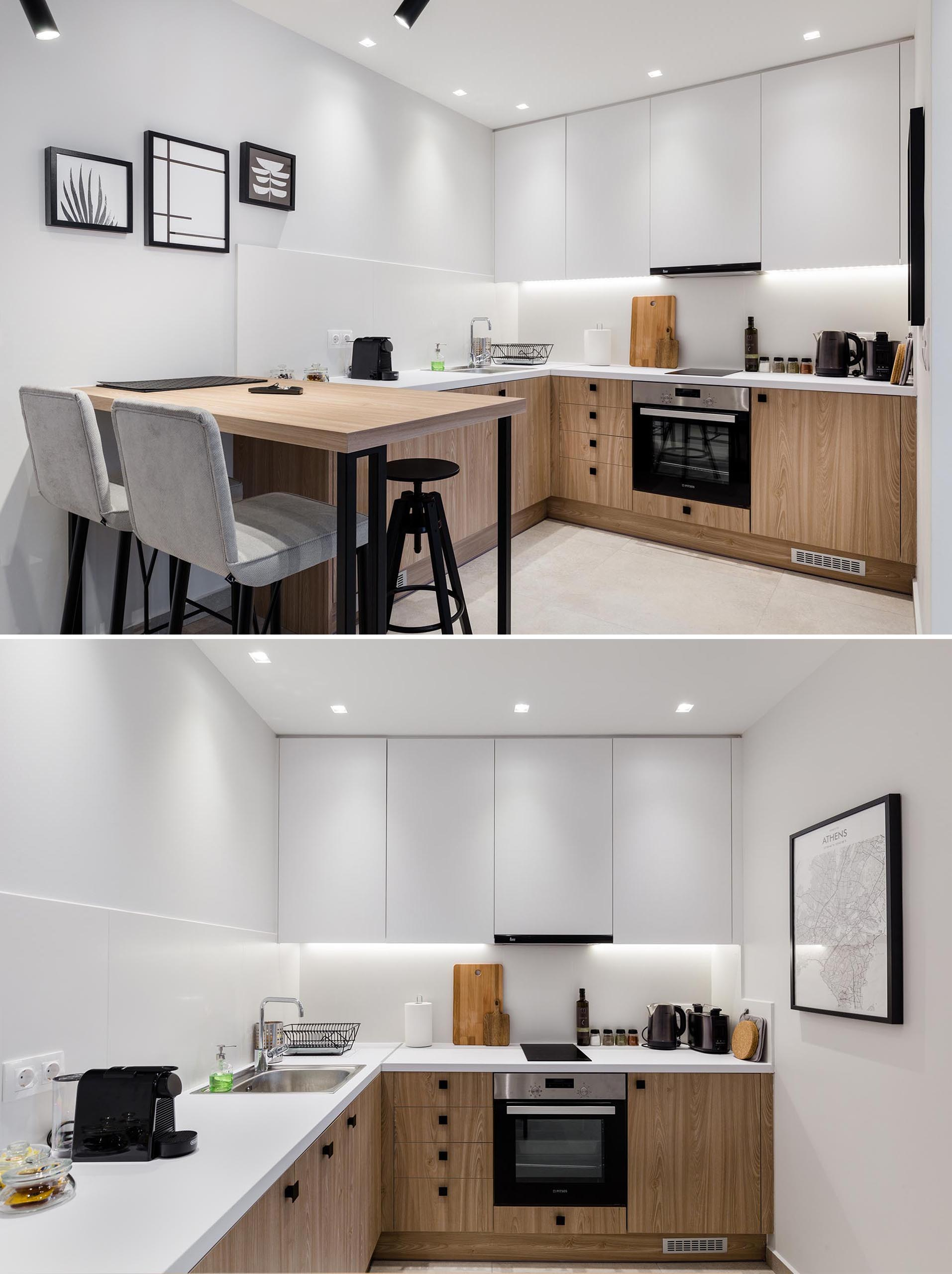 This small apartment has an open interior with a kitchen that features minimalist white upper cabinets and wood lower cabinets, as well as a bar height table.