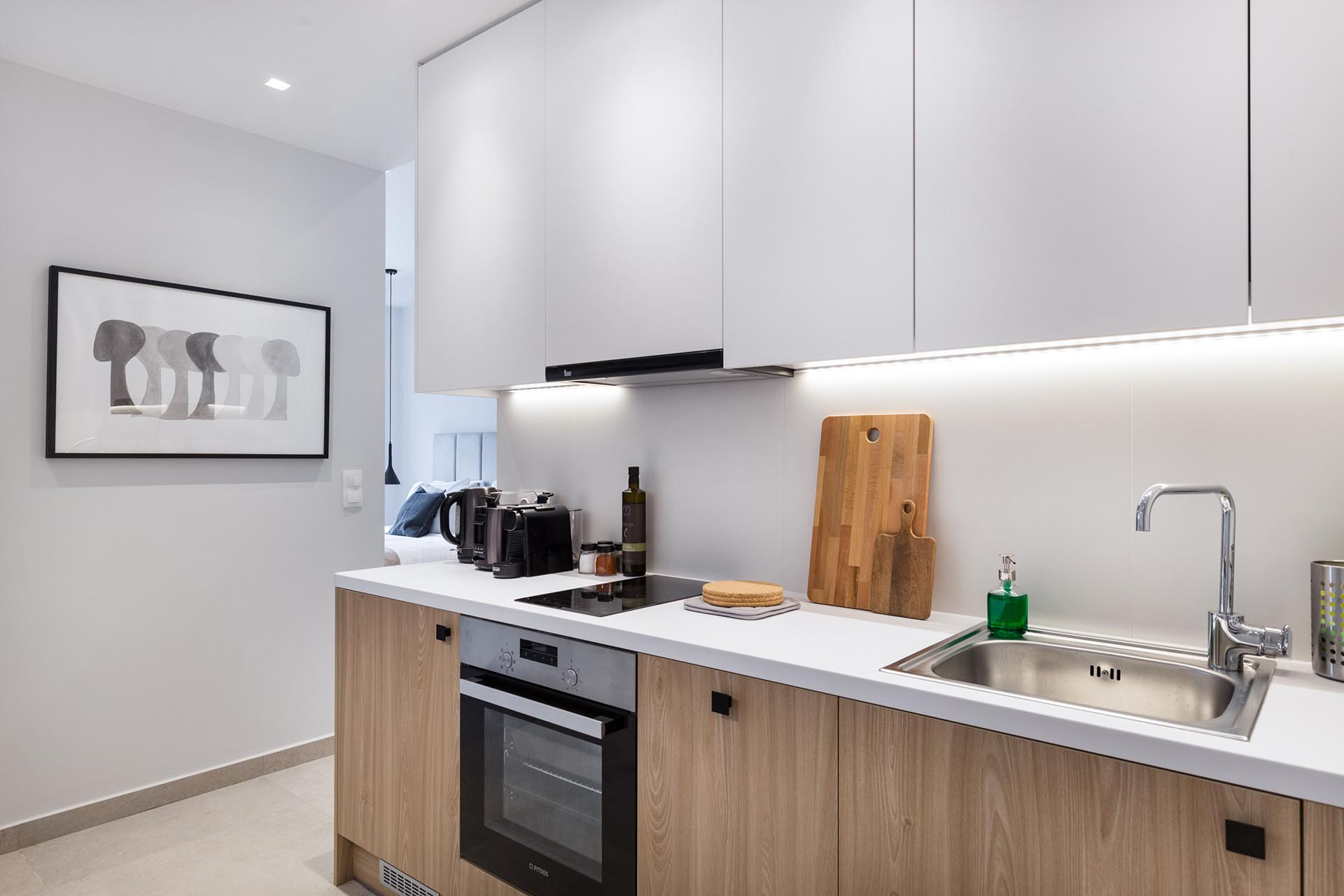 The modern kitchen of a small apartment includes undermount LED lighting.