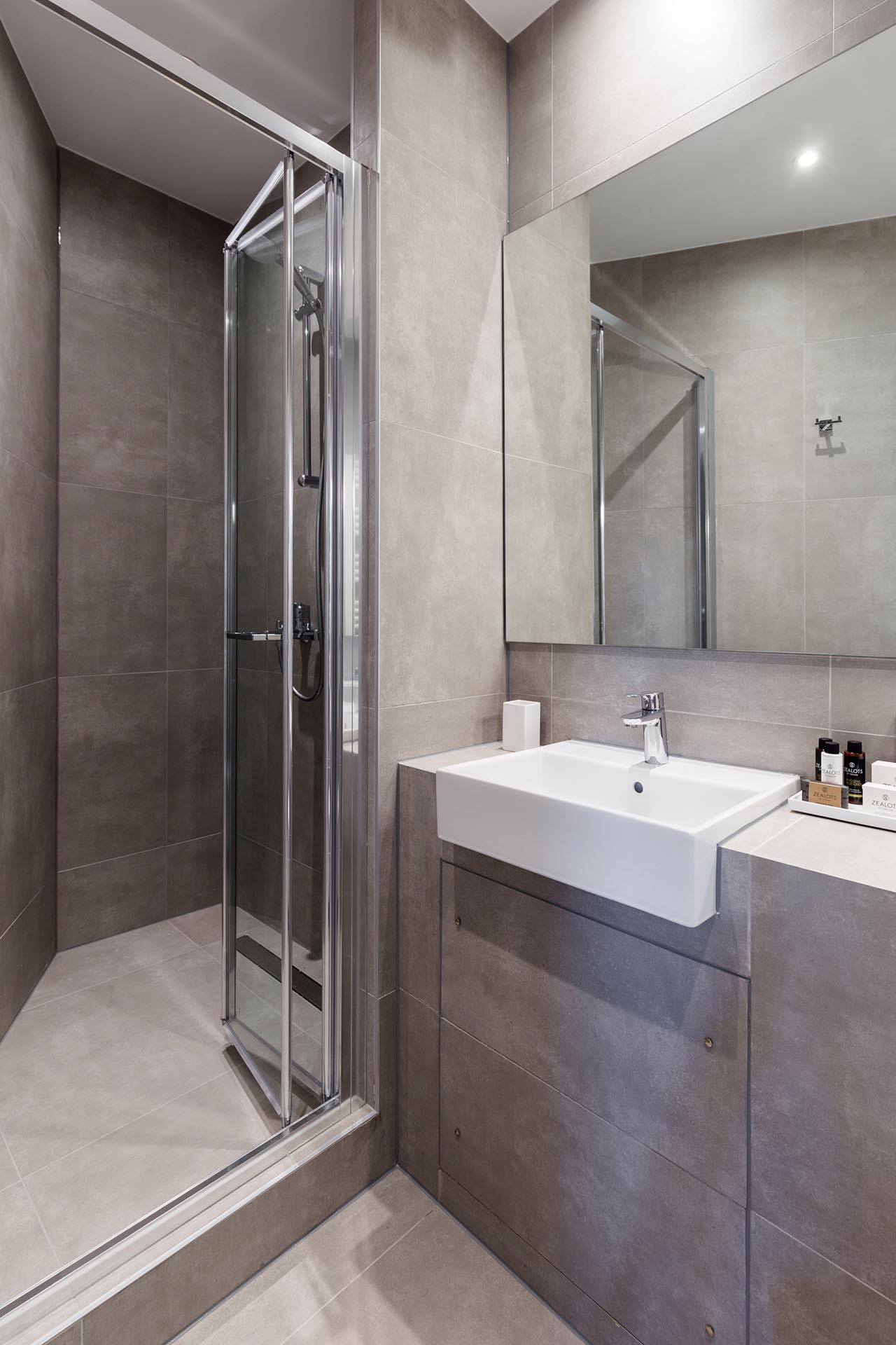 A small and modern bathroom with large format gray tiles.